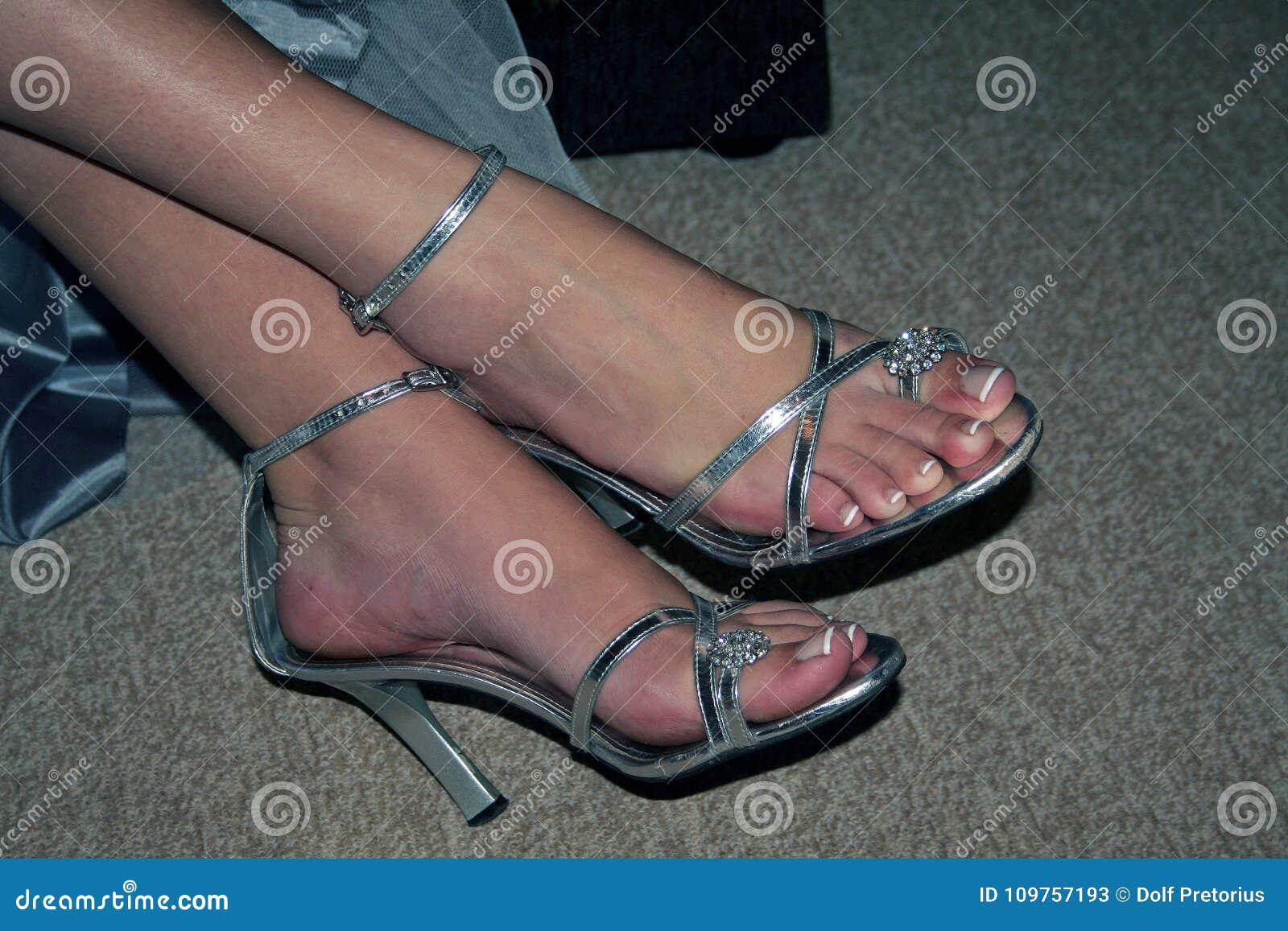 c7c6490abe0 Εικόνα SLR των ποδιών και των αστραγάλων γυναικών ` s στα φανταχτερά ασημένια  παπούτσια με τα υψηλά τακούνια Αστράγαλοι που διασχίζονται δεξιά πέρα από  το ...