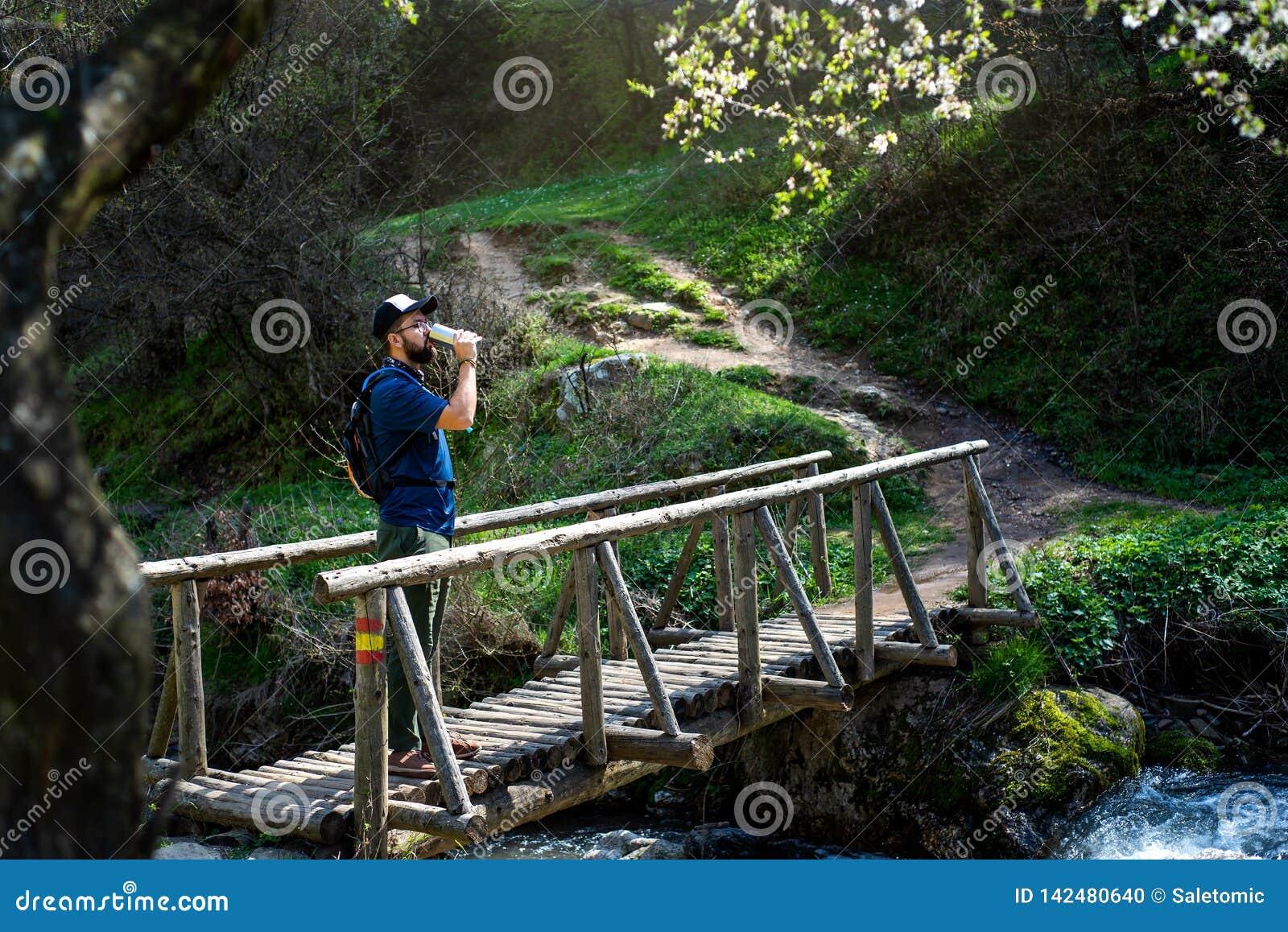 Πόσιμο νερό ατόμων η ξύλινη γέφυρα υπαίθρια
