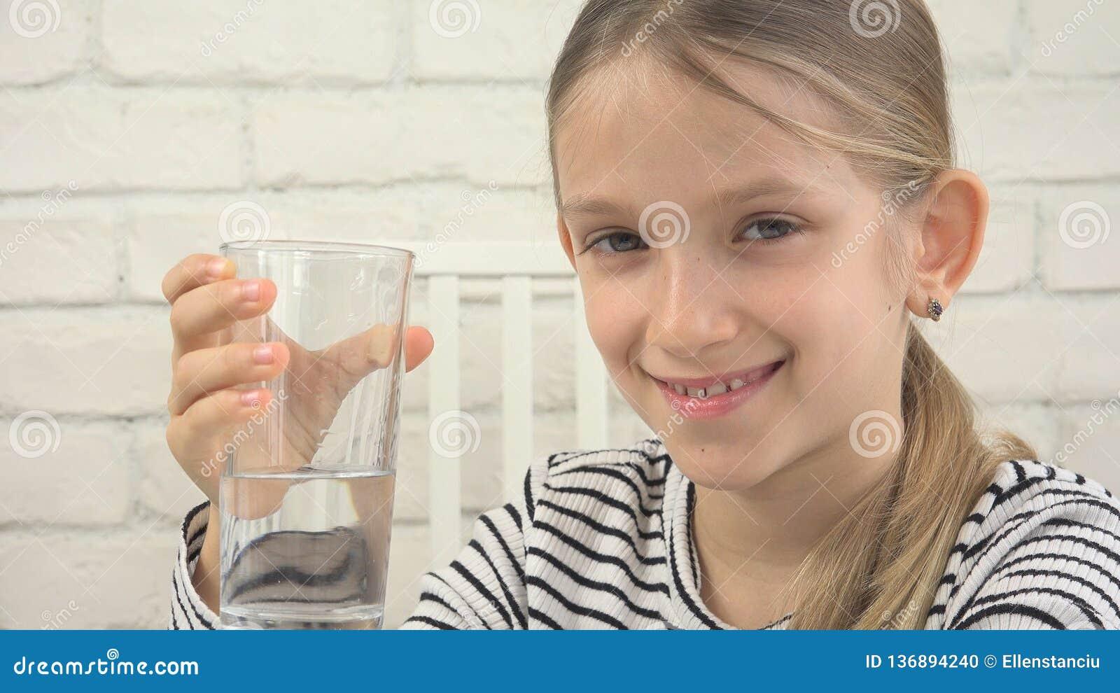 Πόσιμο νερό παιδιών, διψασμένο παιδί που μελετά το γυαλί του γλυκού νερού, κορίτσι στην κουζίνα