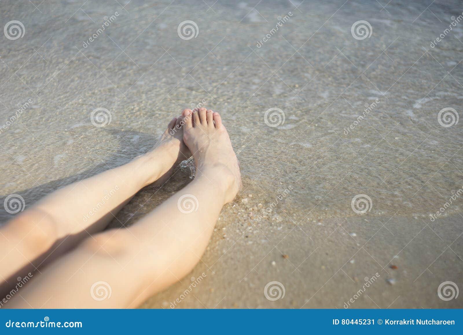 f90a441aa4 Πόδια γυναικών που βάζουν στην παραλία άμμου Πόδια μιας νέας γυναίκας σε  μια παραλία ηλιοθεραπεία