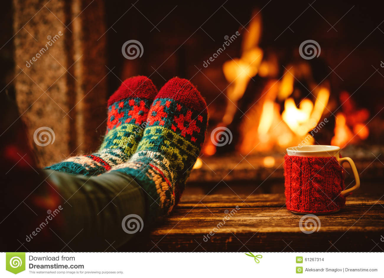 Πόδια στις μάλλινες κάλτσες από την εστία Χριστουγέννων χαλαρώνει τη γυναίκα