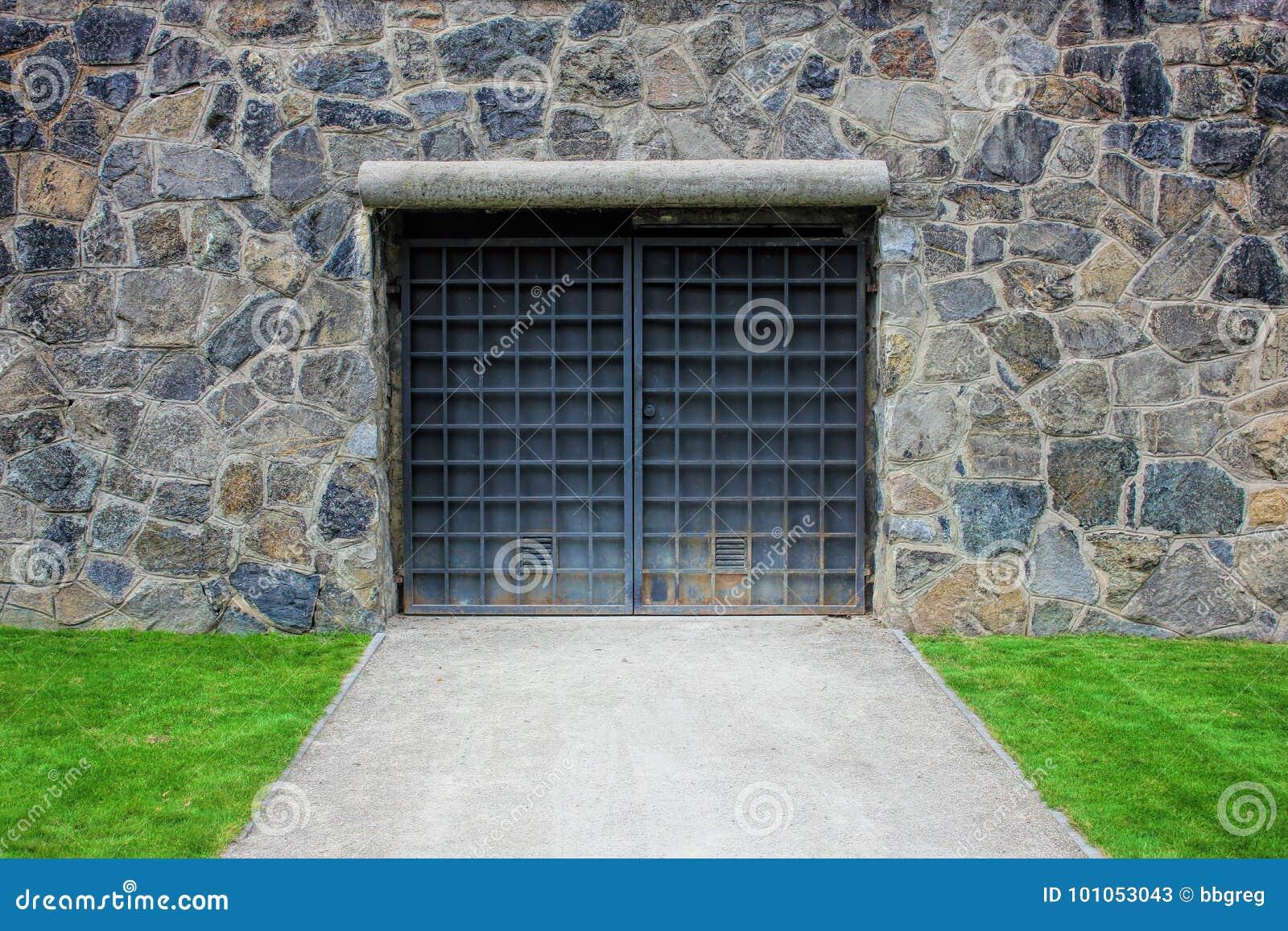 Πύλη μετάλλων ή πόρτα σε έναν παλαιό τοίχο πετρών, γκαράζ, πράσινος χορτοτάπητας