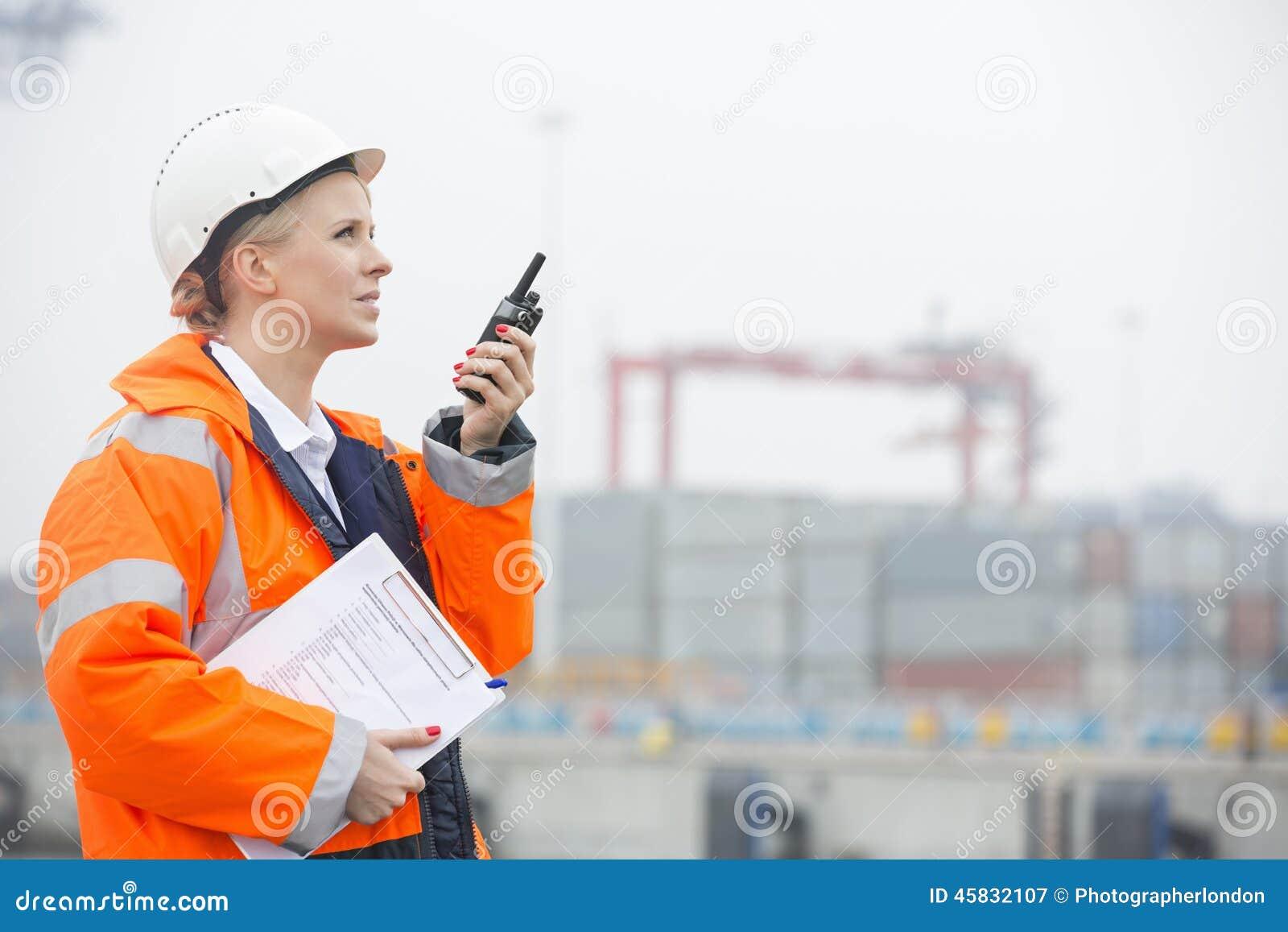 Πλάγια όψη του θηλυκού μηχανικού που χρησιμοποιεί walkie-talkie στη ναυτιλία του ναυπηγείου