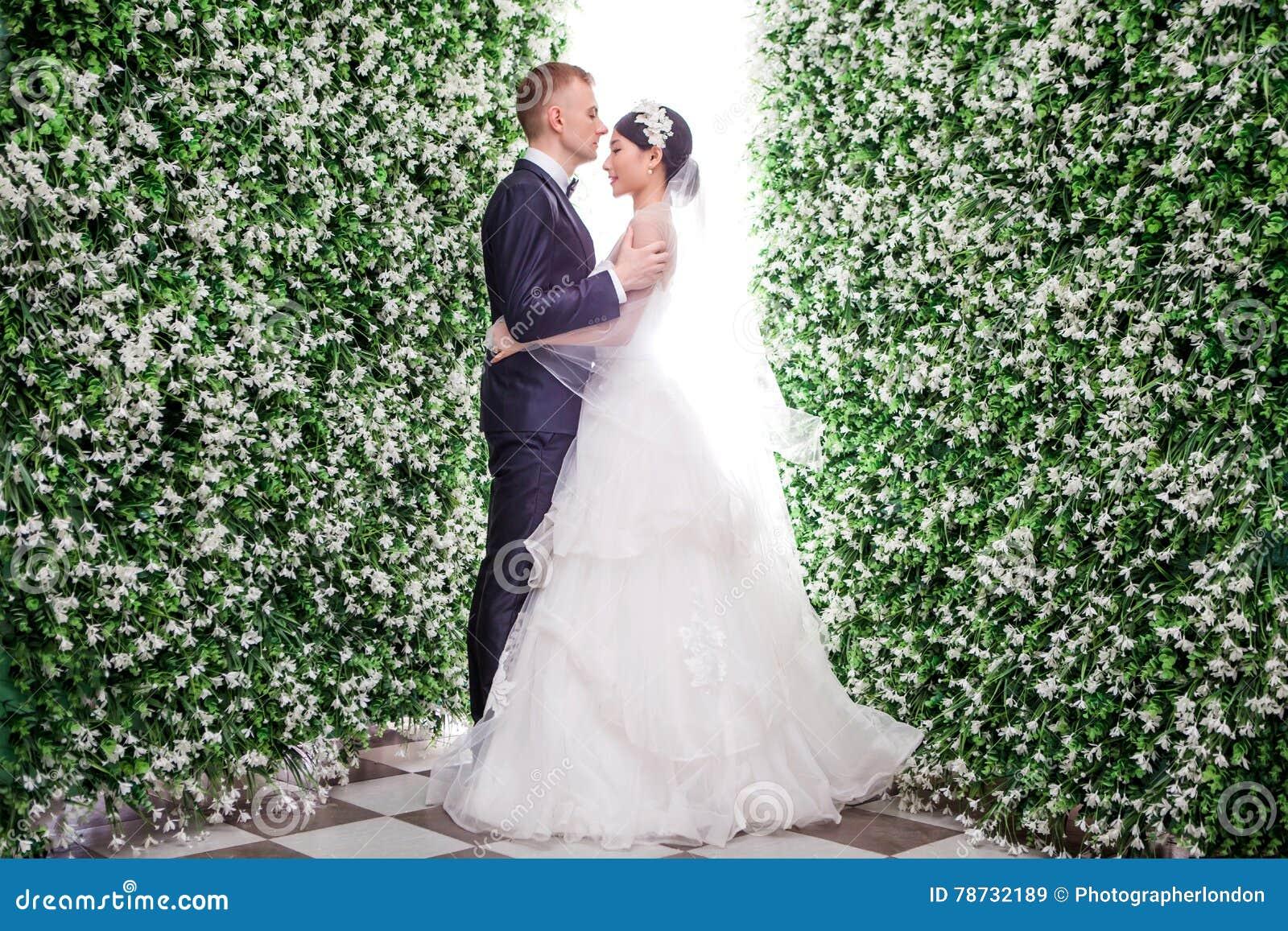 Πλάγια όψη του ρομαντικού γαμήλιου ζεύγους που στέκεται στη μέση των διακοσμήσεων λουλουδιών