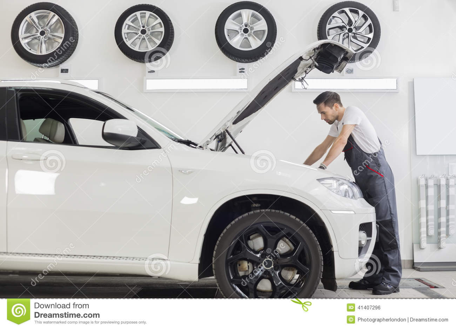 Πλήρης πλάγια όψη μήκους της αρσενικής μηχανικής μηχανής αυτοκινήτων εξέτασης στο κατάστημα επισκευής