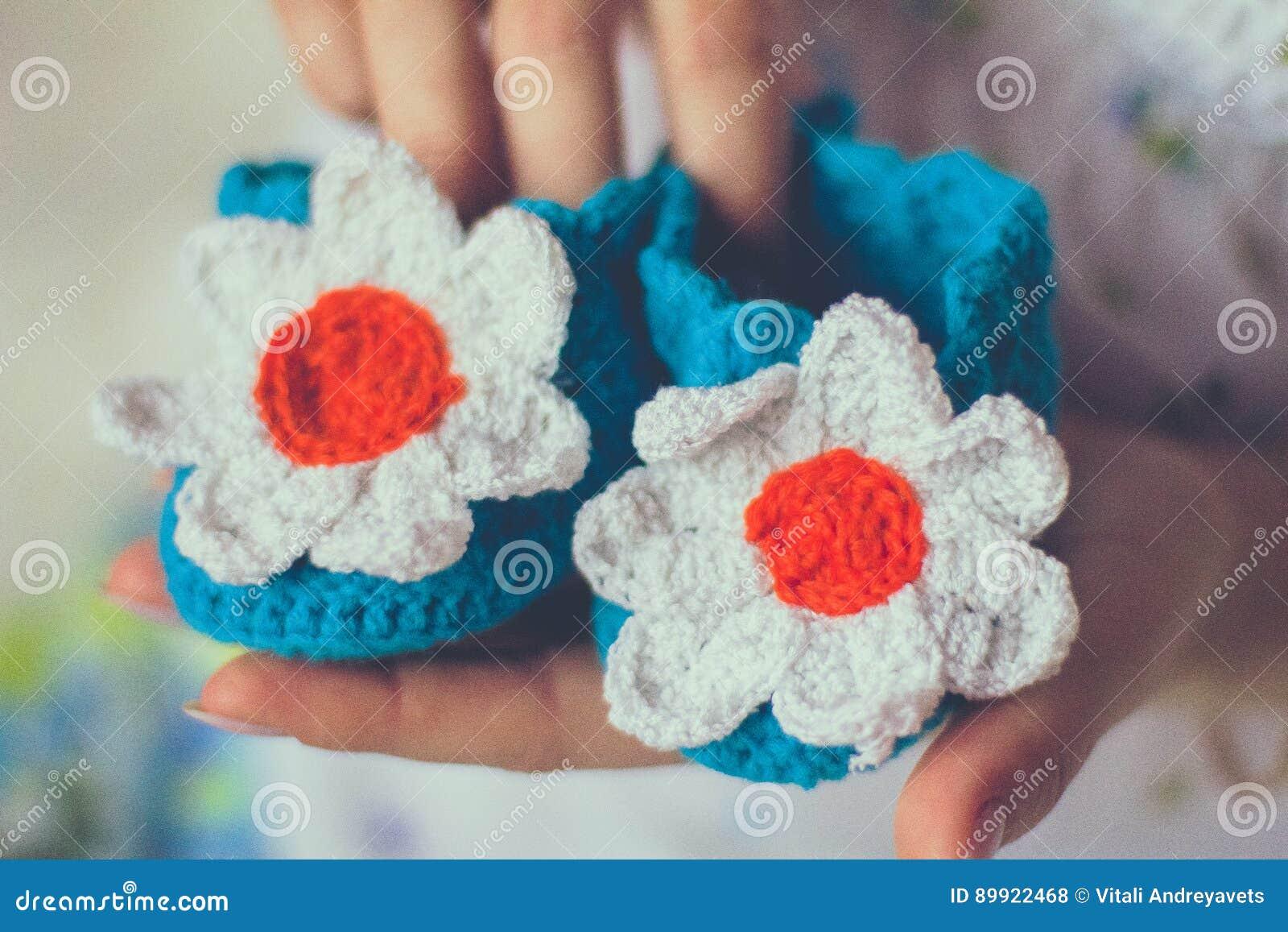 Πλεκτές μωρό παντόφλες στα χέρια