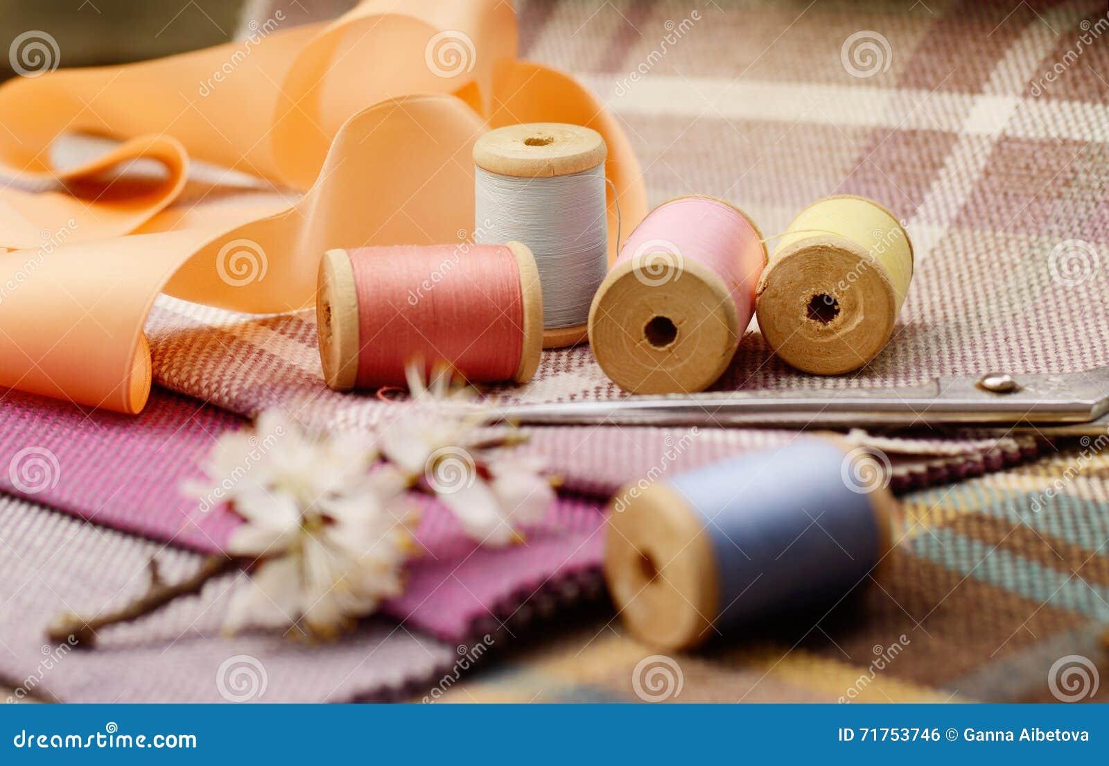Ράβοντας προμήθειες, βελόνες, ψαλίδι στο ζωηρόχρωμο gunny υφαντικό υπόβαθρο