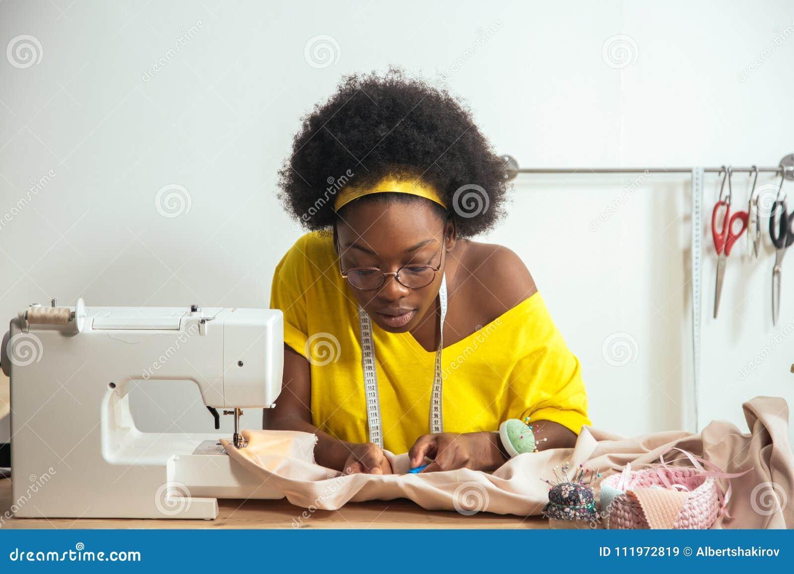 Ράβοντας ύφασμα με τη βελόνα seamstress στον εργασιακό χώρο
