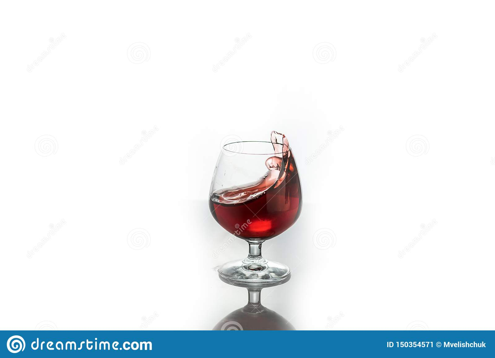 Ράντισμα κόκκινου κρασιού από ένα γυαλί, που απομονώνεται στο λευκό