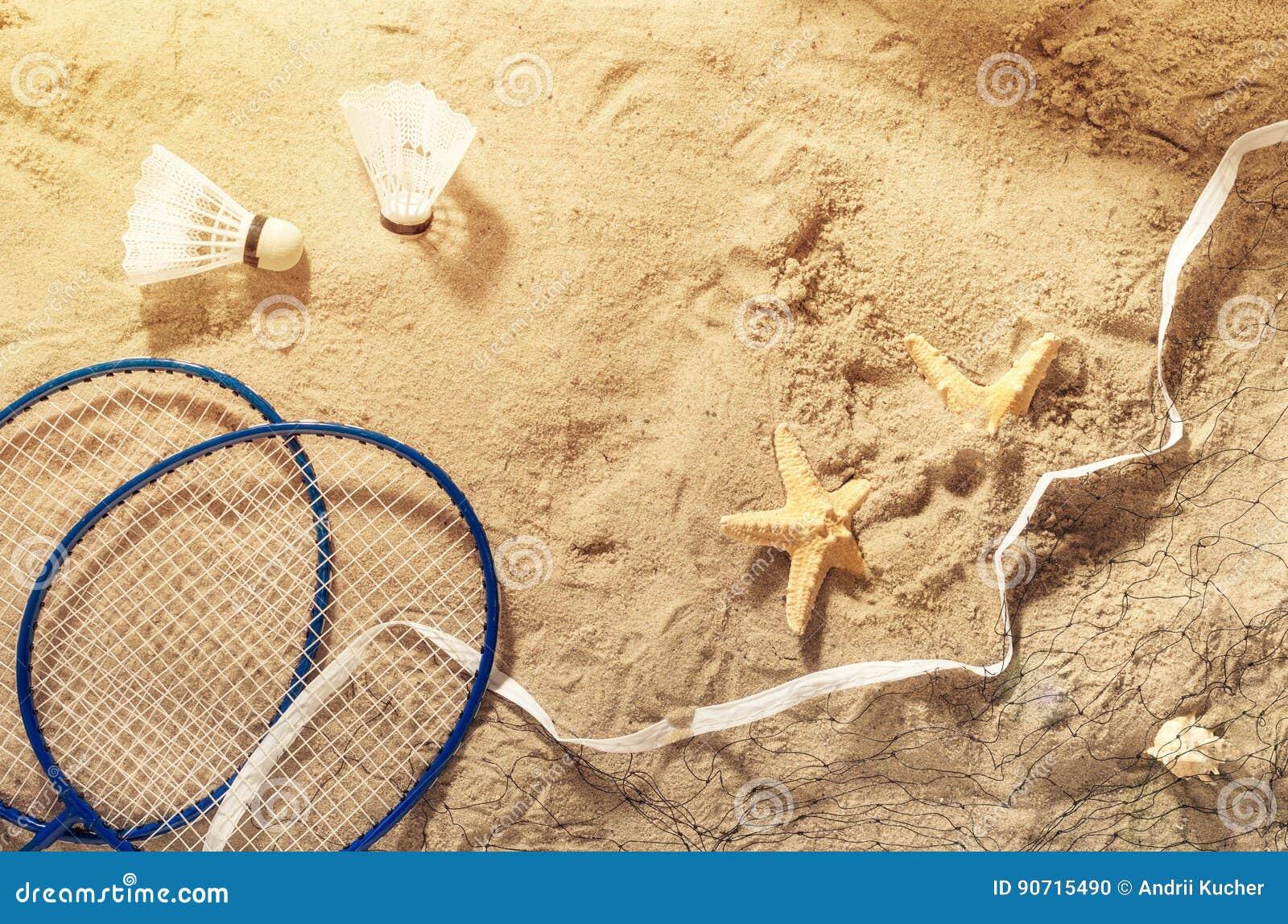 Ρακέτες μπάντμιντον, καθαρές, shuttlecock και αστερίας στην άμμο