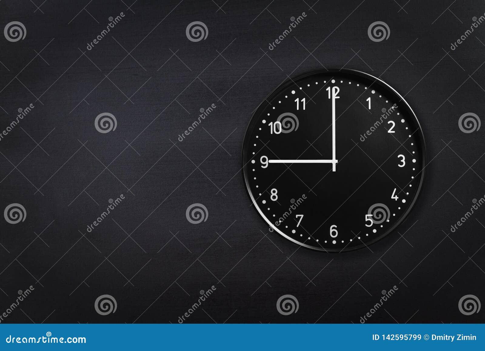 Ρολόι τοίχων που παρουσιάζει εννέα η ώρα στο μαύρο υπόβαθρο πινάκων κιμωλίας Ρολόι γραφείων που παρουσιάζει 9am ή 9pm στη μαύρη σ