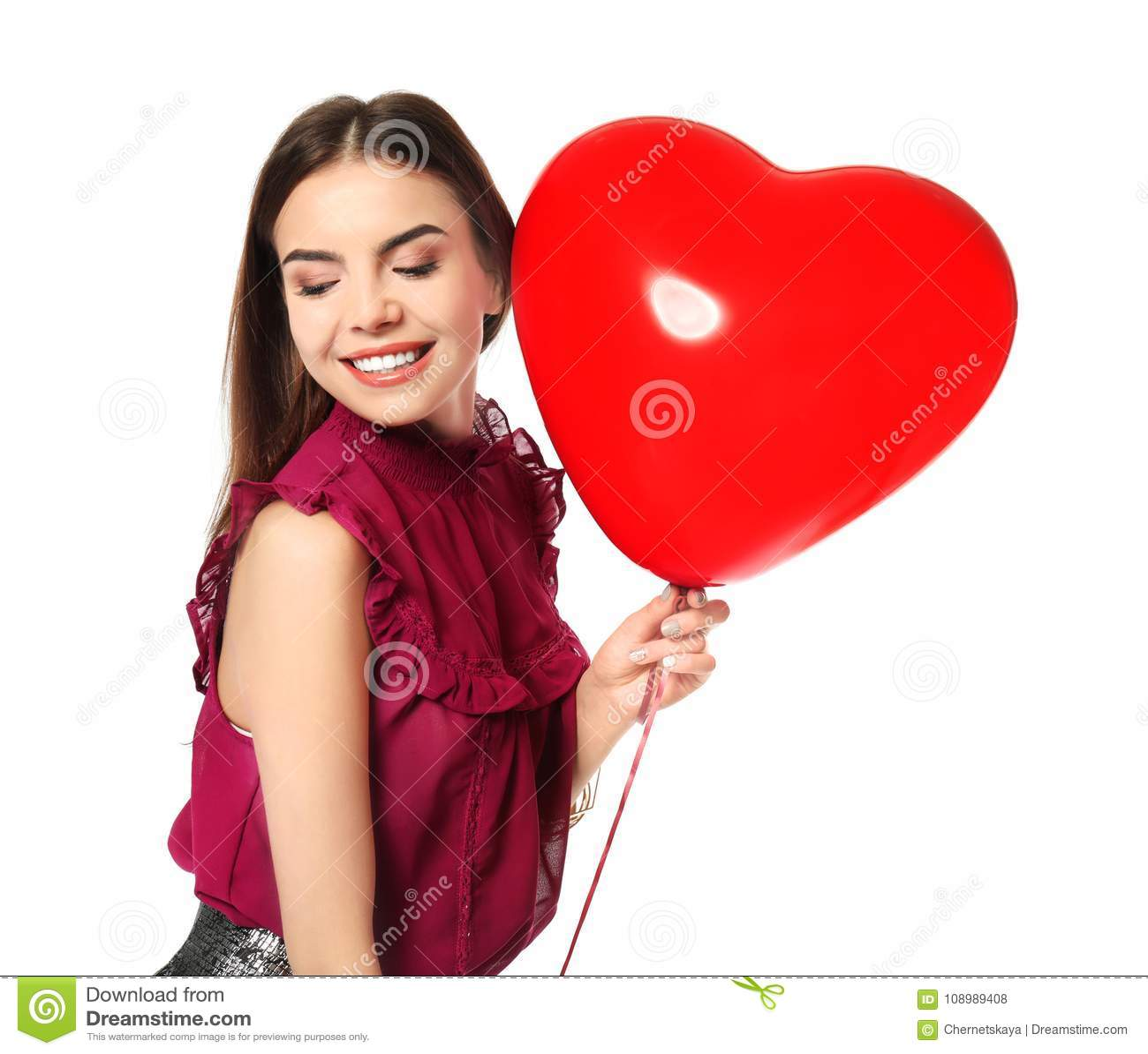 Ρομαντική νέα γυναίκα με το καρδιά-διαμορφωμένο μπαλόνι για την ημέρα βαλεντίνων ` s