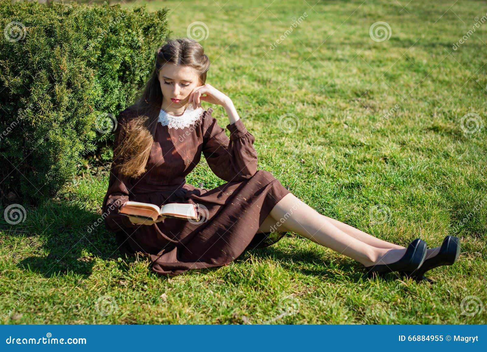 Ρομαντική νέα γυναίκα που διαβάζει ένα βιβλίο στη συνεδρίαση κήπων στη χλόη Χαλαρώστε την υπαίθρια χρονική έννοια