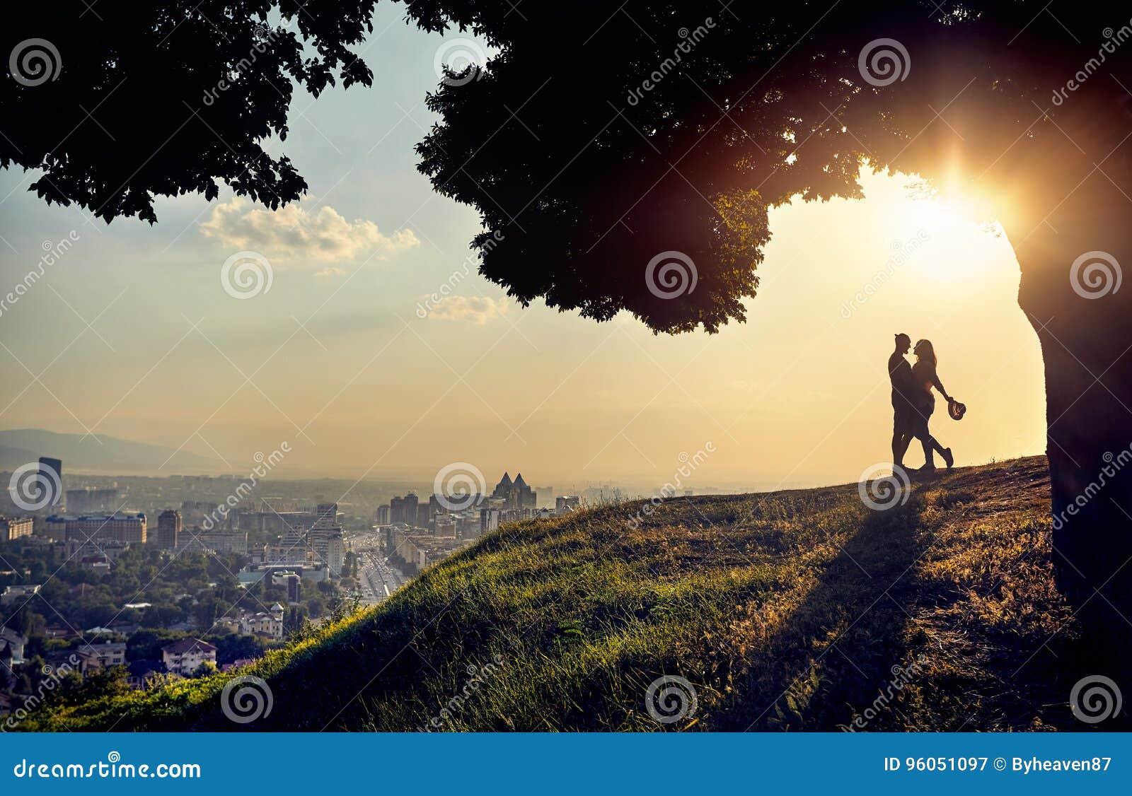 Ρομαντικό ζεύγος στην άποψη πόλεων ηλιοβασιλέματος