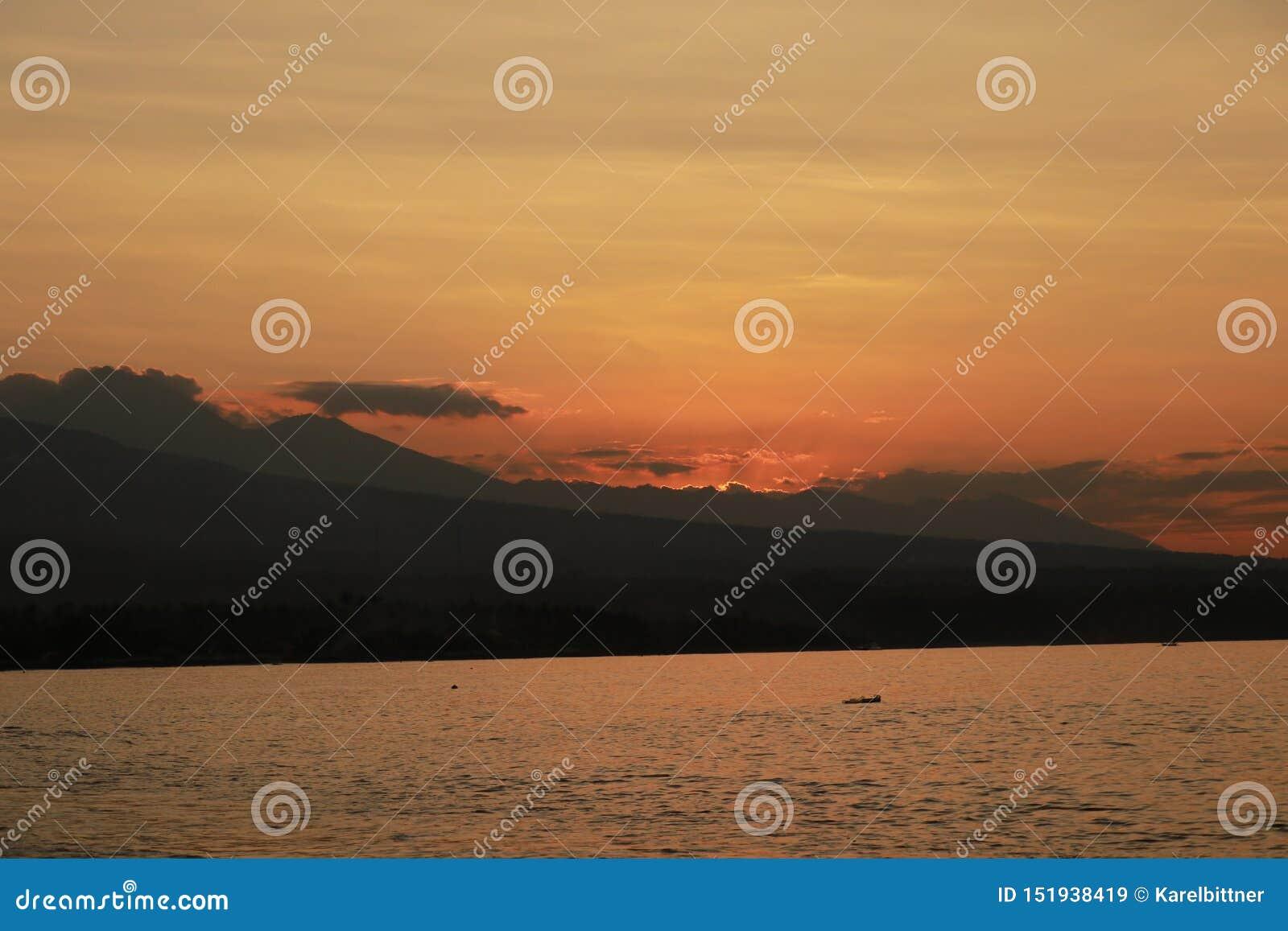 Ρομαντικό ηλιοβασίλεμα στην παραλία στην Ινδονησία Το Surfer πηγαίνει να απολαύσει paddleboard στο ηλιοβασίλεμα Πανόραμα ακτών με