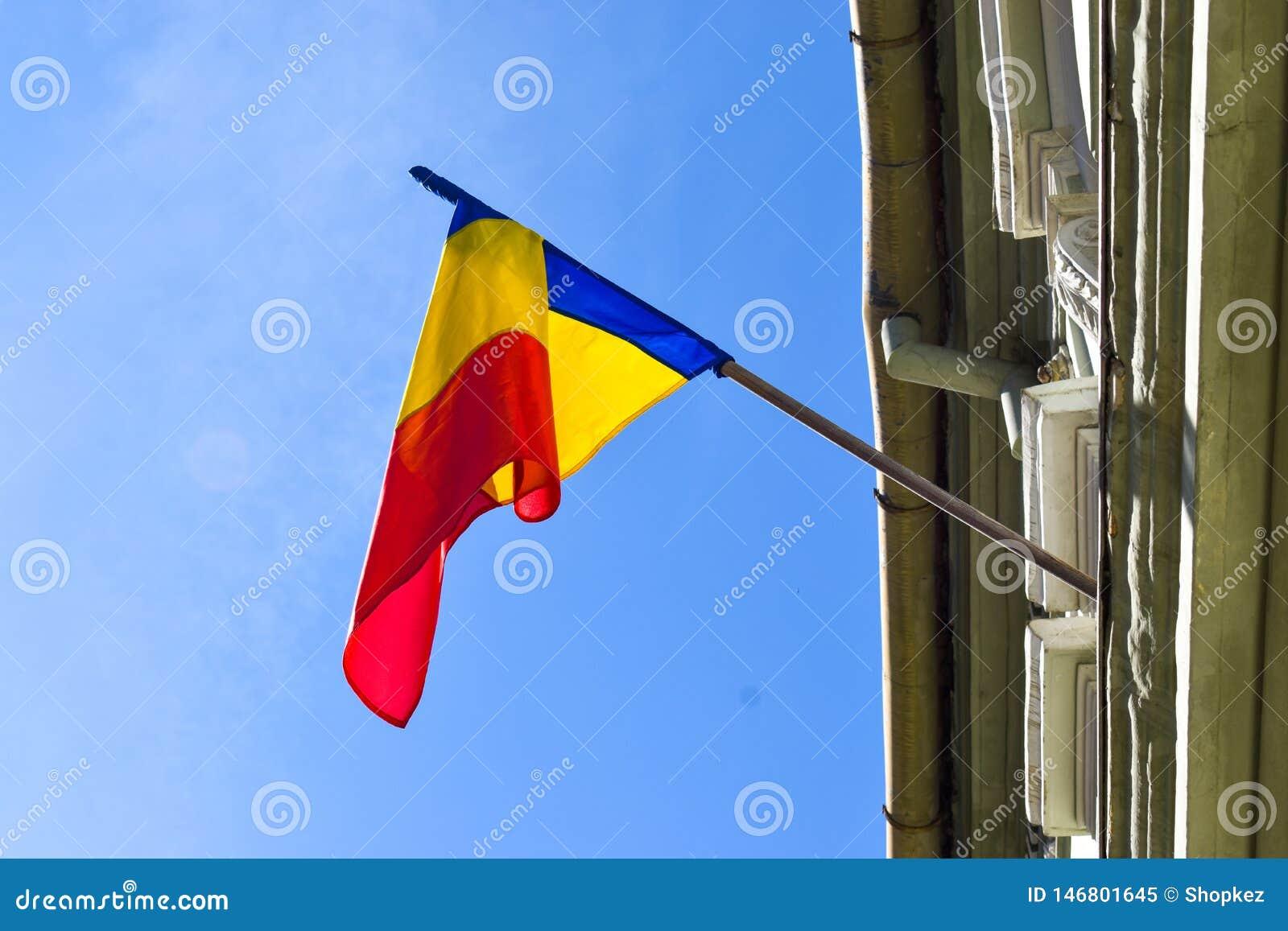 Ρουμανική κυματίζοντας σημαία στο κτήριο ενάντια στο μπλε ουρανό