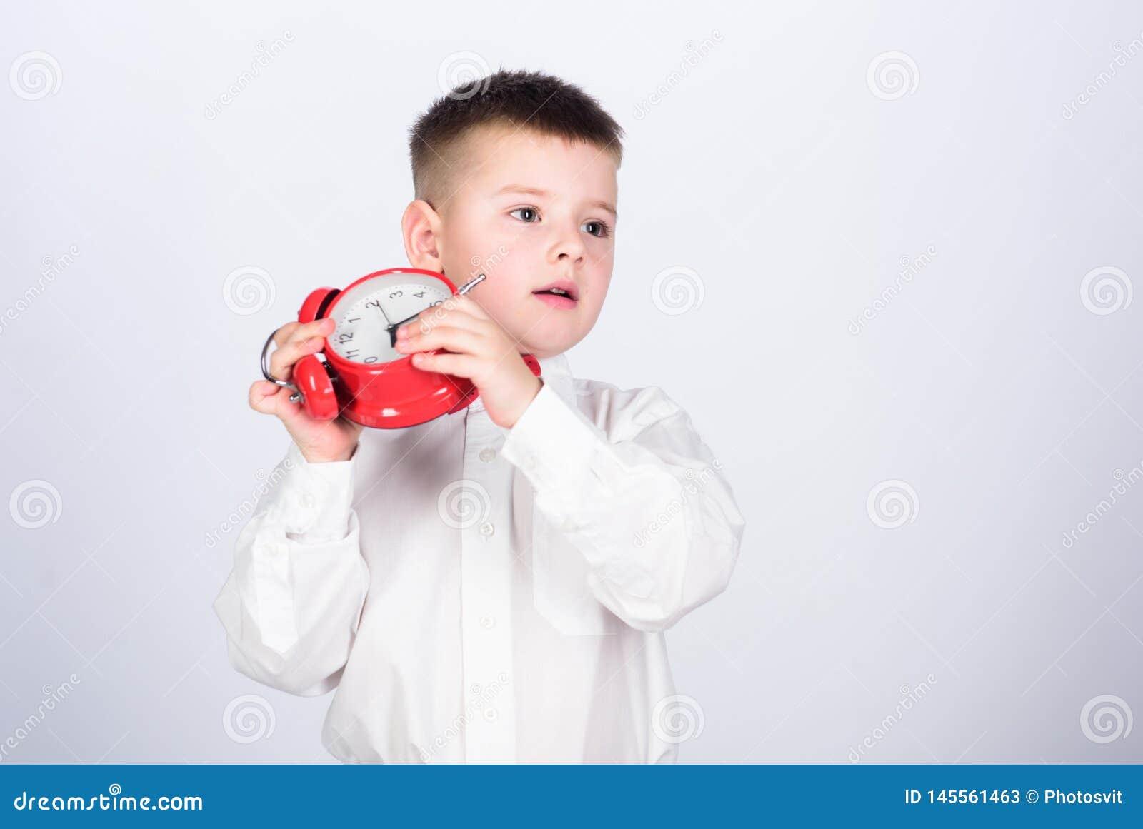 Ρουτίνα πρωινού Μαθητής με το ξυπνητήρι Παιδιών λατρευτός αγοριών άσπρος δεσμός τόξων πουκάμισων κόκκινος Αναπτύξτε τη μόνη πειθα