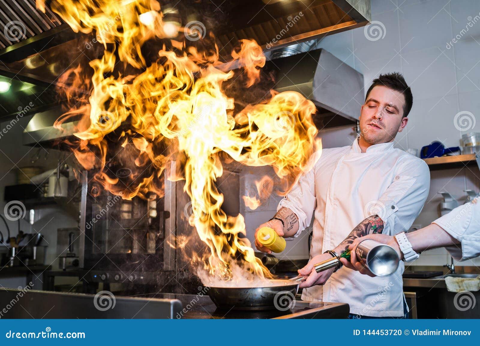 Ρωσία, Αγία Πετρούπολη, 03 17 2019 - ο αρχιμάγειρας κάνει flambe σε μια κουζίνα εστιατορίων, σκοτεινό υπόβαθρο