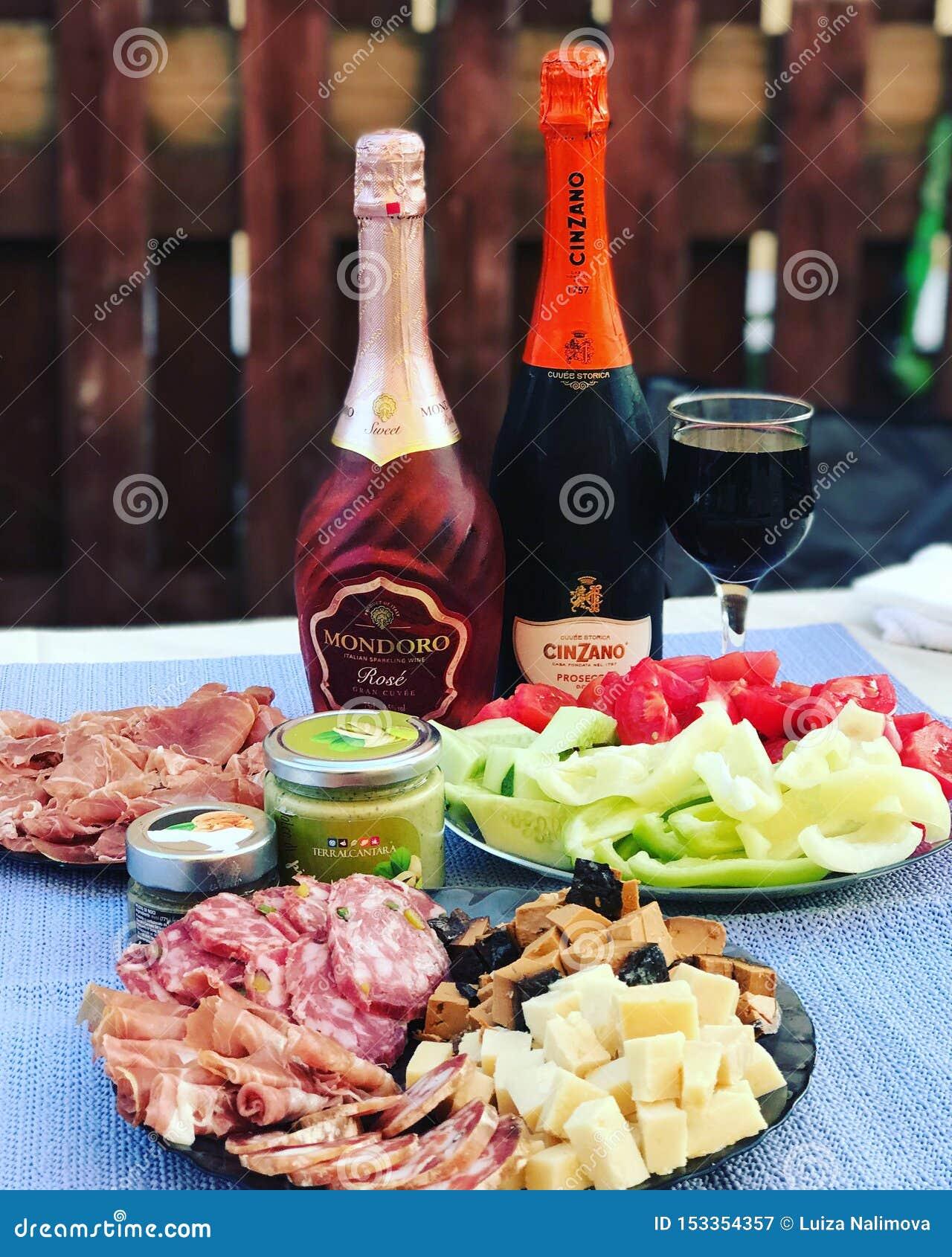 Ρωσία, Ταταρία, στις 27 Ιουλίου 2018 Ένα μπουκάλι του proseco Cinzano, ένα μπουκάλι Mondoro αυξήθηκε, πρόχειρα φαγητά: jamon, τυρ