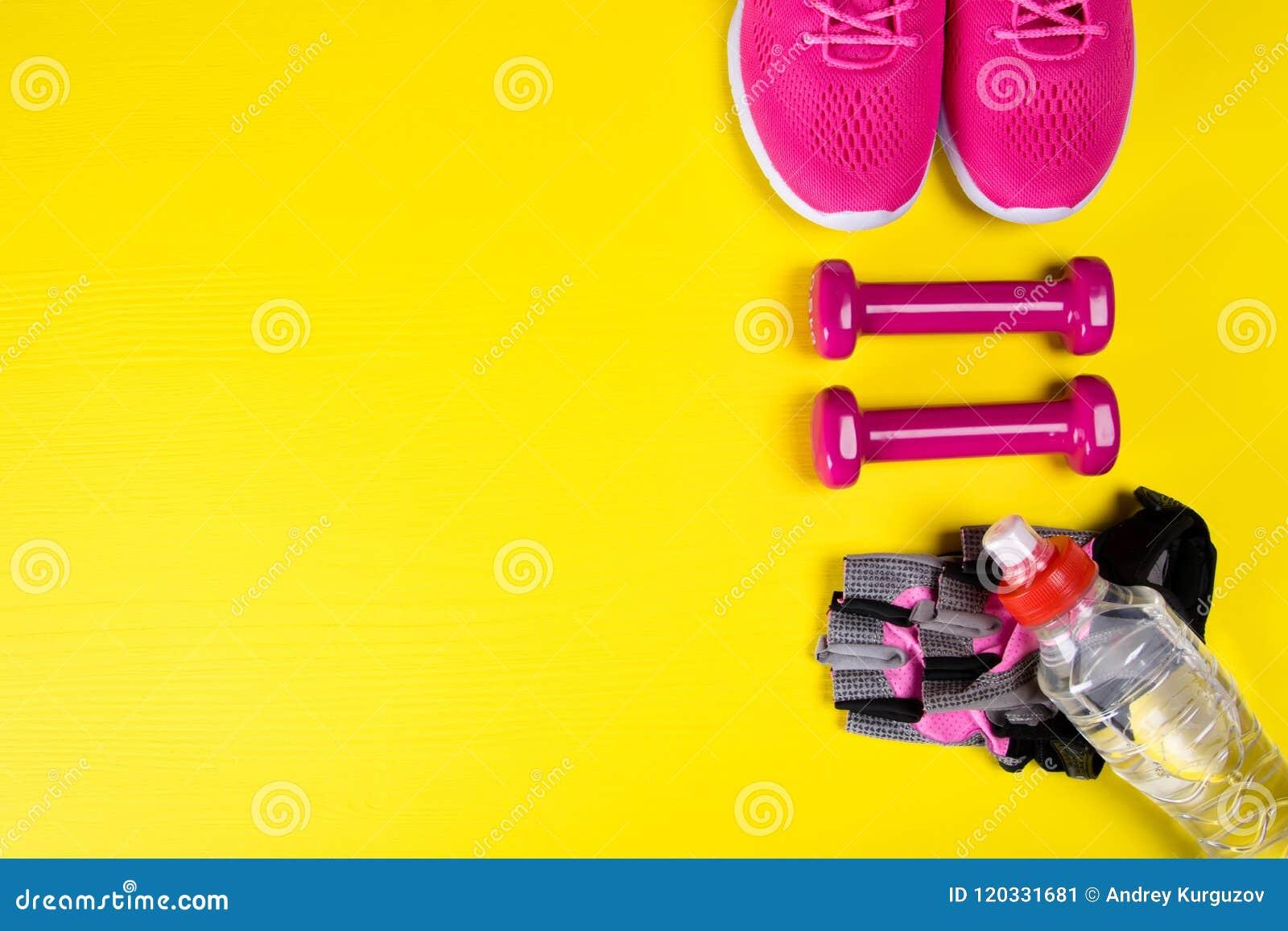 Ρόδινα πάνινα παπούτσια και εξαρτήματα για την ικανότητα, και ένα μπουκάλι νερό, σε ένα κίτρινο υπόβαθρο, με μια θέση για το γράψ