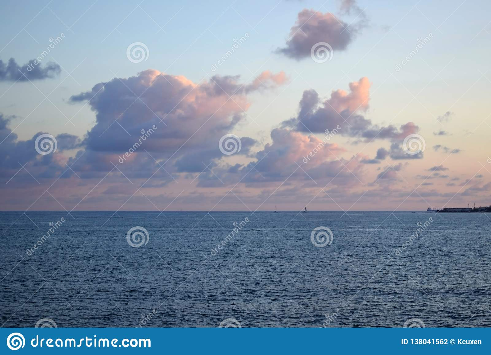 Ρόδινα χνουδωτά σύννεφα πέρα από τη θάλασσα