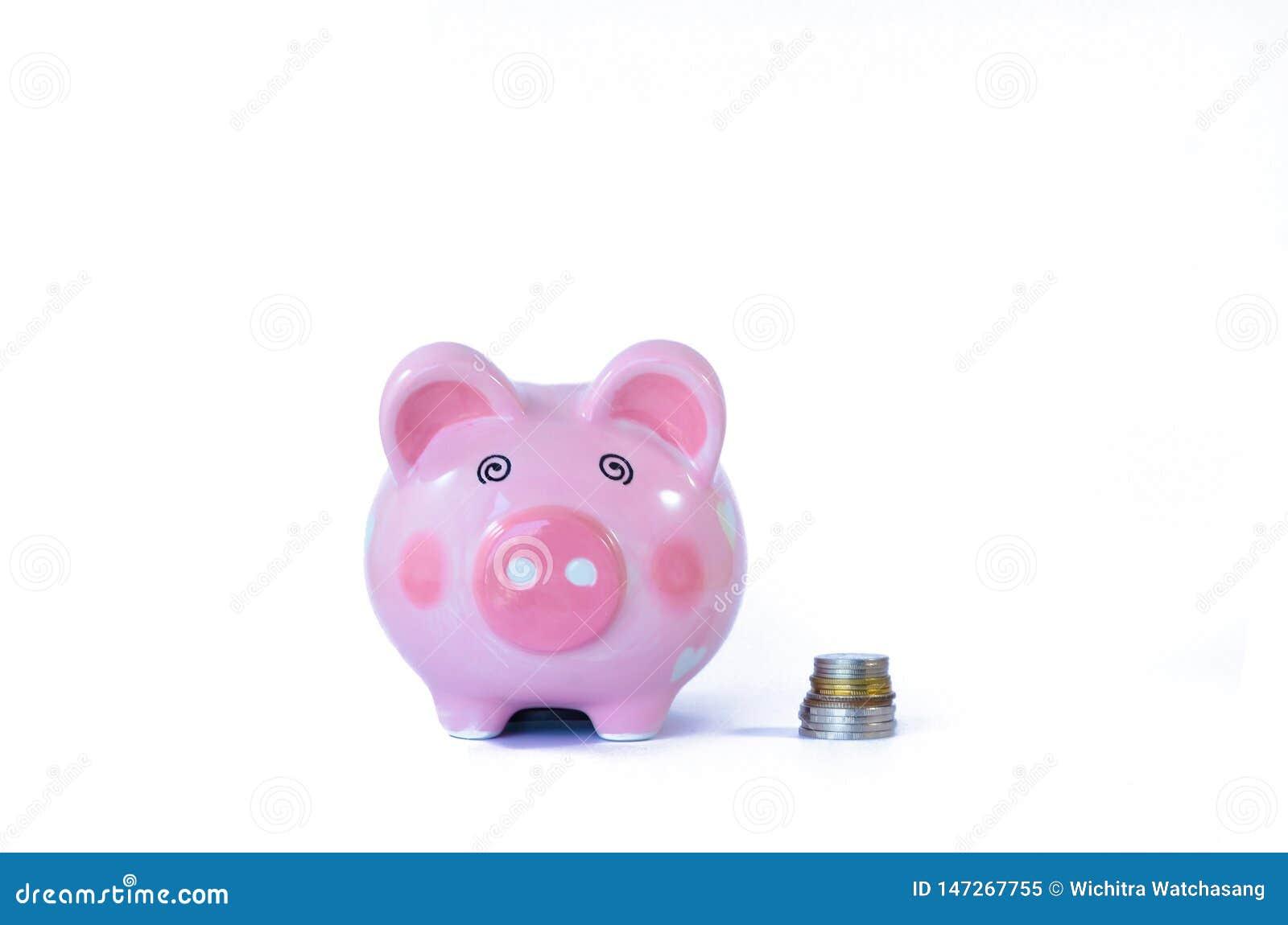 Ρόδινα piggy τράπεζα και νομίσματα που απομονώνονται στο λευκό