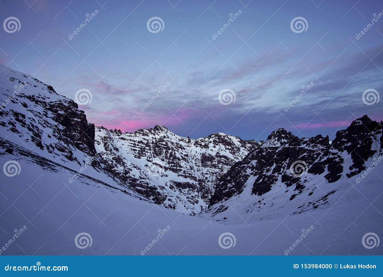 Ρόδινη ανατολή πέρα από τα χιονισμένα υψηλά βουνά ατλάντων