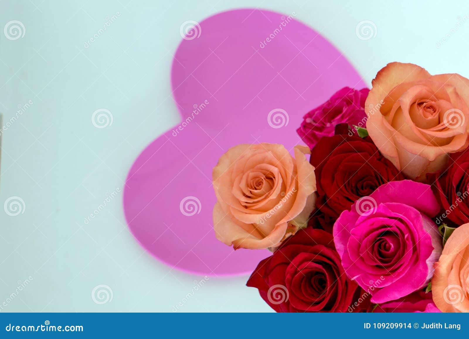 Ρόδινη καρδιά στο κέντρο με τα ρόδινα και κόκκινα τριαντάφυλλα στη δεξιά γωνία