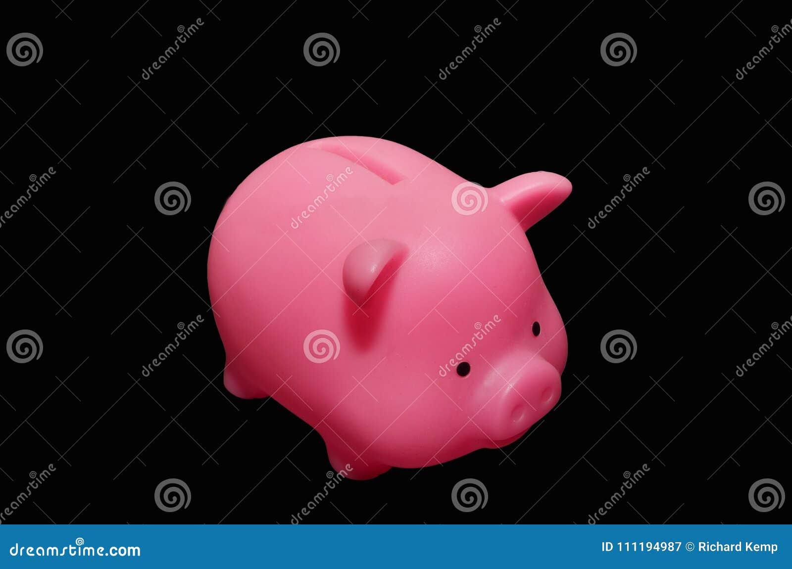 Ρόδινη piggy τράπεζα με το μαύρο υπόβαθρο