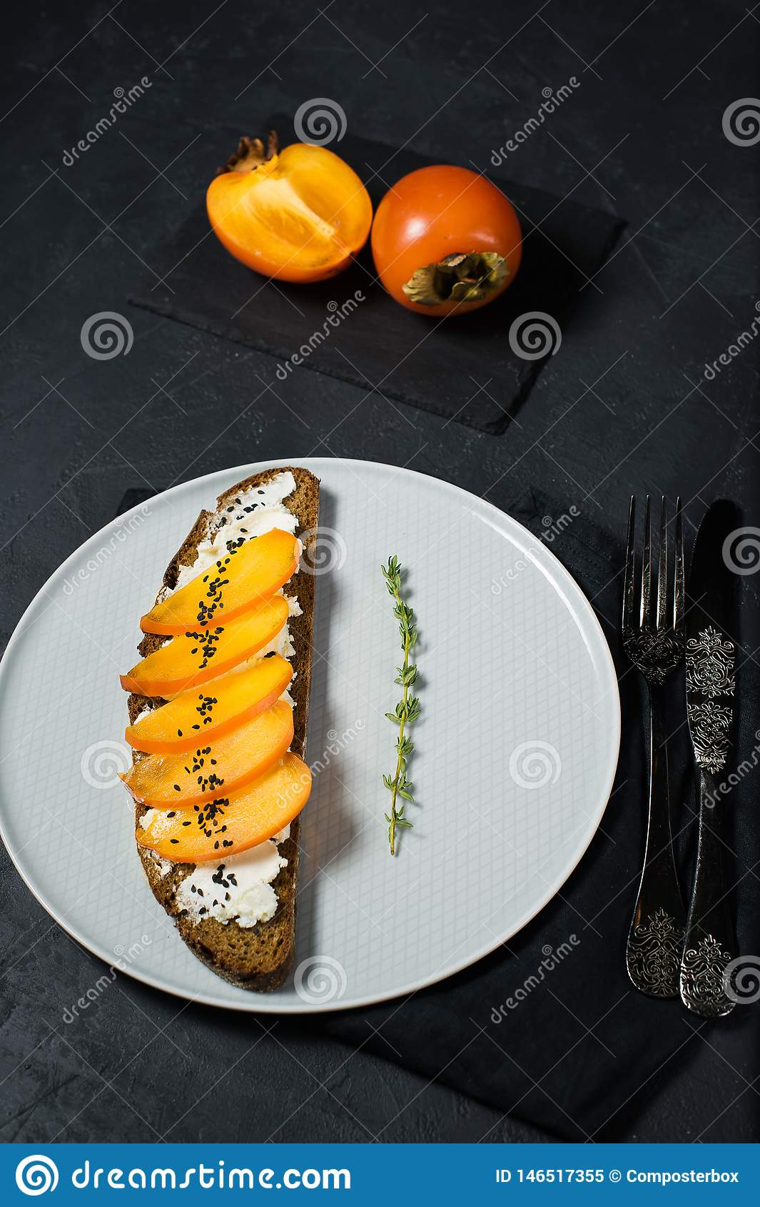 Σάντουιτς με persimmon και μαλακό τυρί σε ένα μαύρο υπόβαθρο