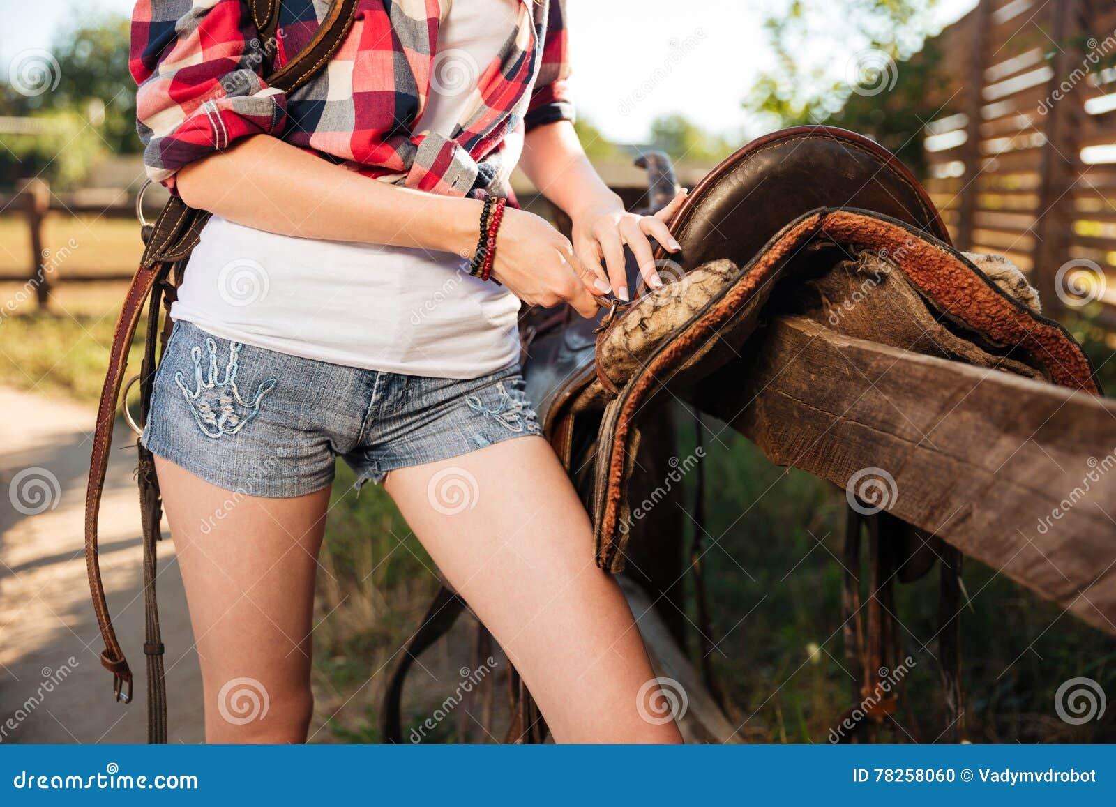 Σέλα που προετοιμάζεται για την ιππασία από τη νέα γυναίκα cowgirl