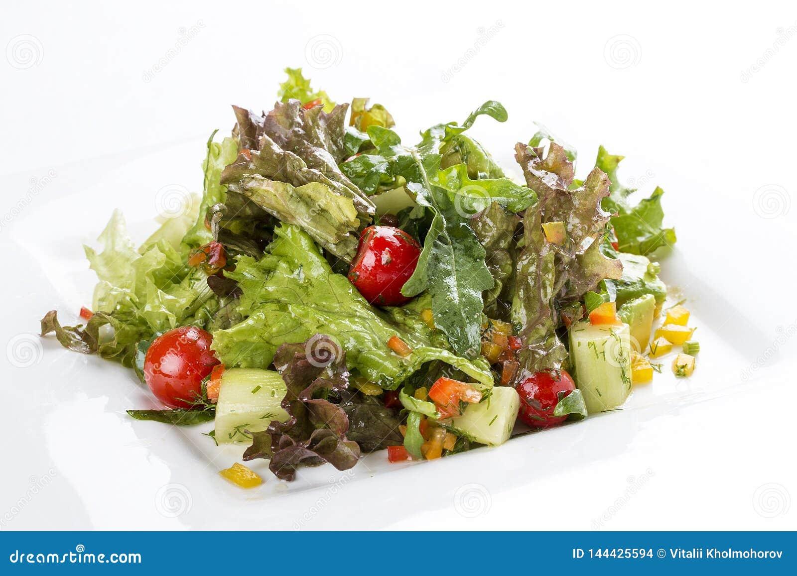 Σαλάτα με το αβοκάντο και λαχανικά σε ένα άσπρο πιάτο