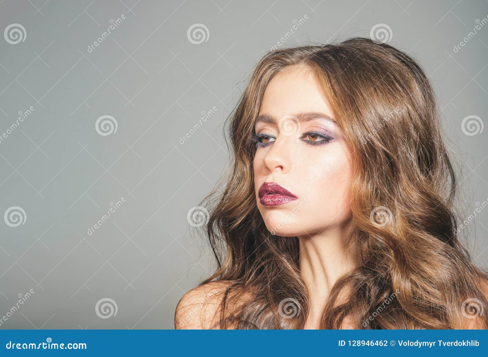 Σαλόνι και κομμωτής ομορφιάς γυναίκα με τη μόδα makeup και τη μακροχρόνια σγουρή τρίχα Κορίτσι με τη γοητεία Makeup πορτρέτο μόδα