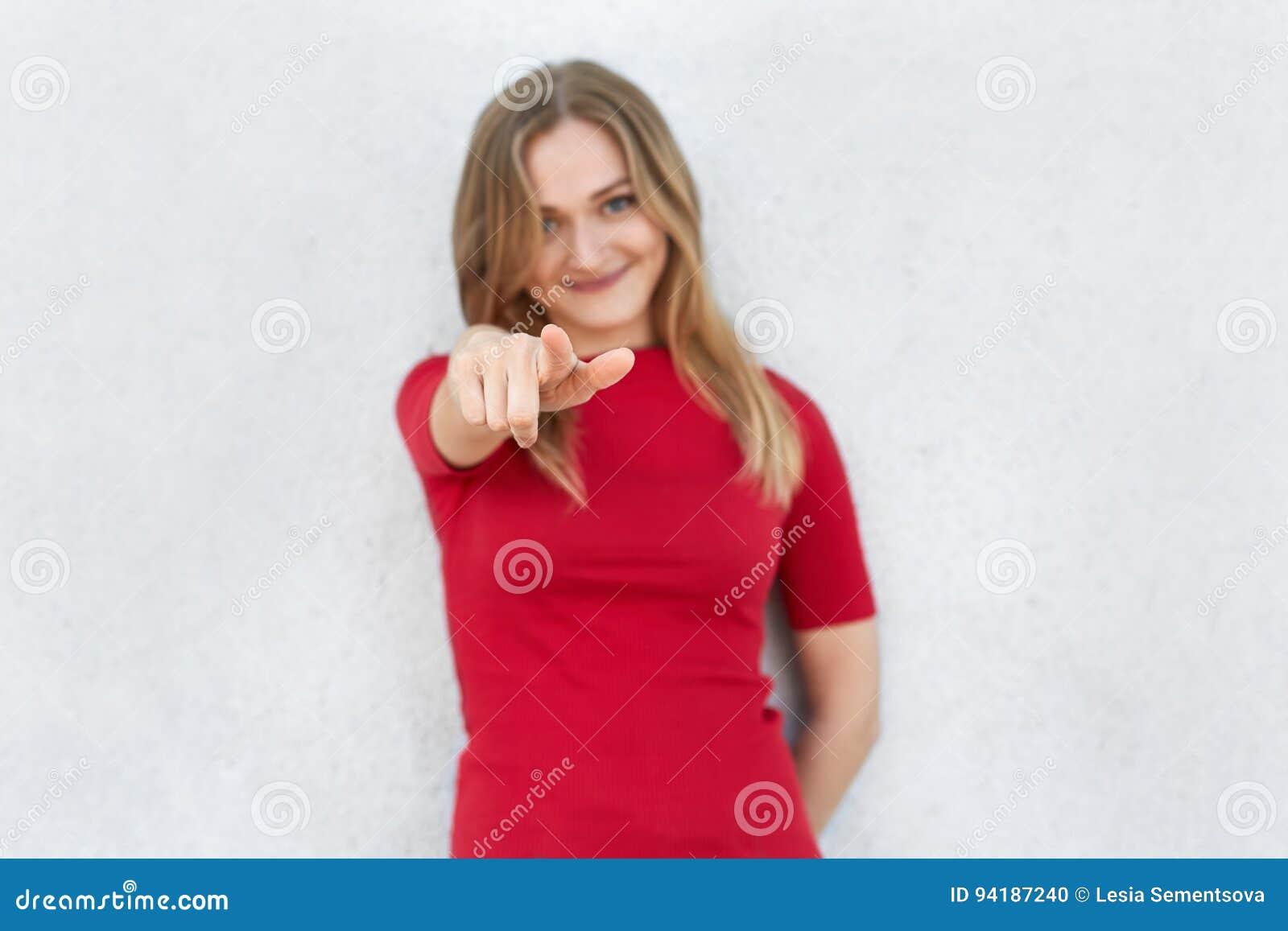 Σας επιλέγω! Καλλιεργημένος πυροβολισμός της γυναίκας στην κόκκινη υπόδειξη φορεμάτων στη κάμερα με το αντίχειρα που απομονώνεται