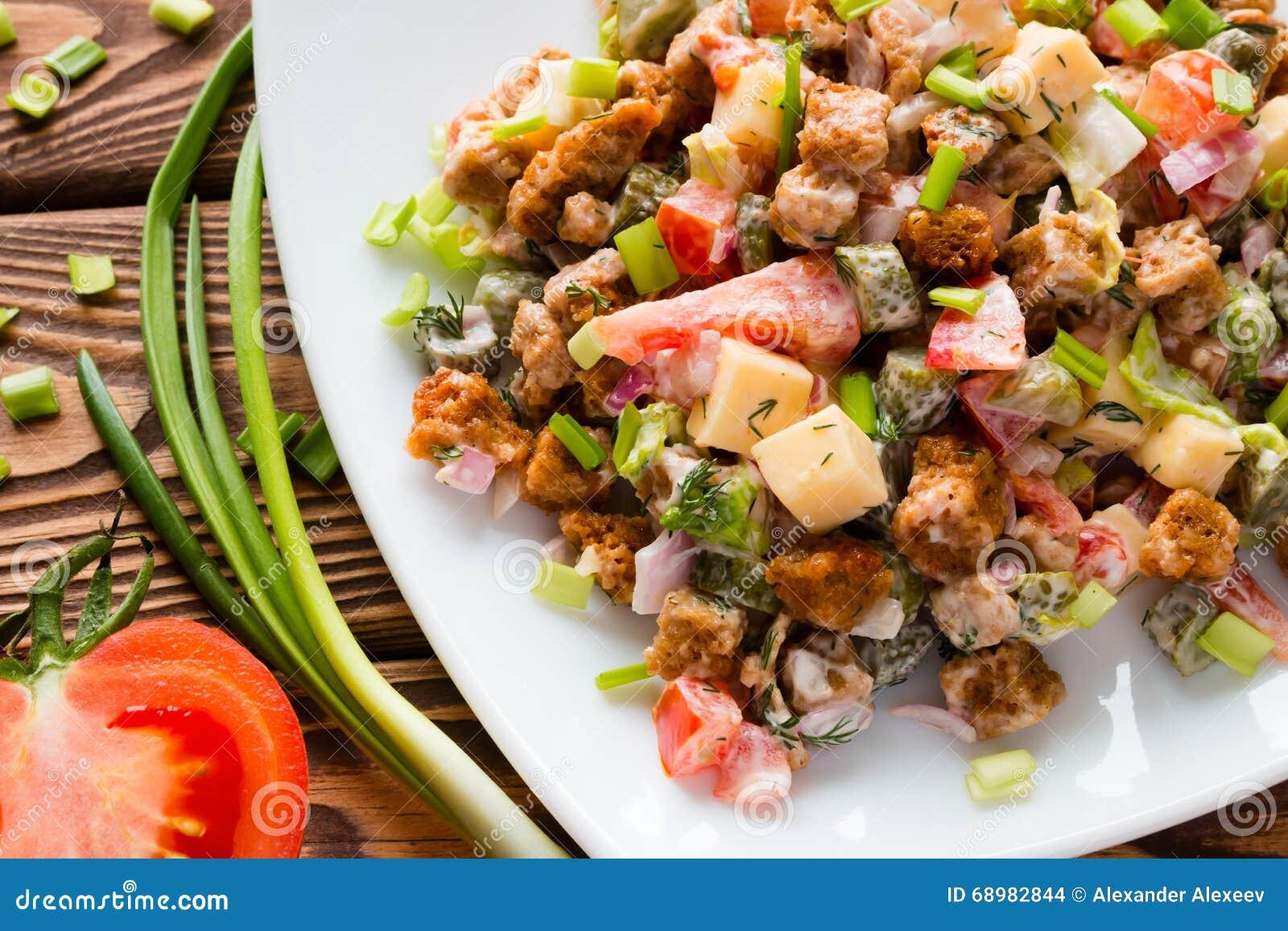 Σαλάτα με τη μαγιονέζα κοντά στα πράσινα κρεμμύδια και μισή ντομάτα
