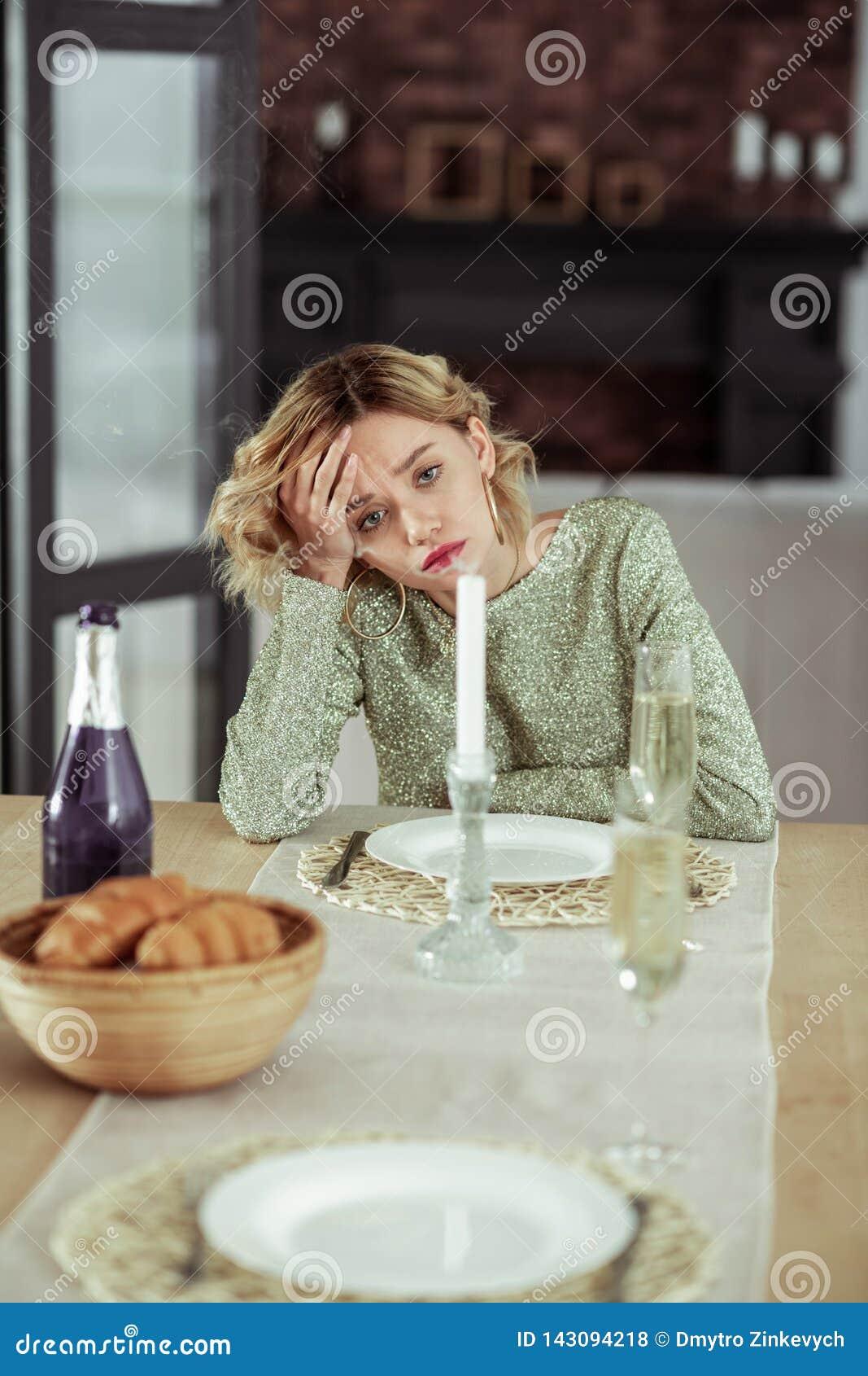 Σγουρή ξανθή σύζυγος που αισθάνεται τη μελαγχολική παραμονή μόνος στο σπίτι