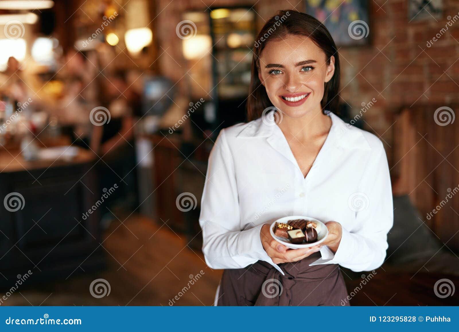 Σερβιτόρα στον καφέ Γυναίκα με τις καραμέλες σοκολάτας στη βιομηχανία ζαχαρωδών προϊόντων