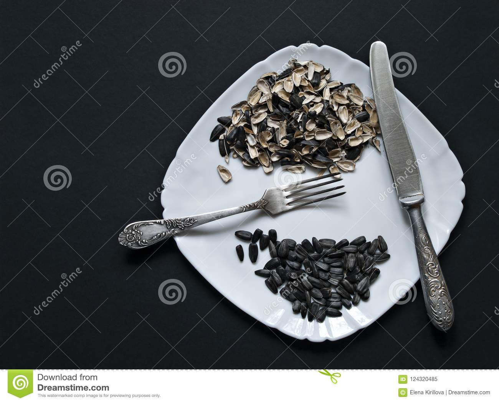 Σε ένα άσπρο πιάτο οι σπόροι ενός ηλίανθου, ο φλοιός από