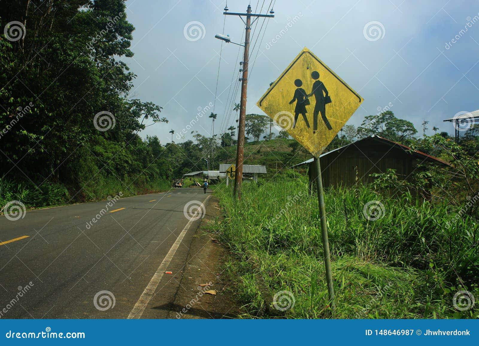 Σημάδι δίπλα στο δρόμο σε ένα μικρό χωριό που λέει ότι υπάρχει ένα σχολείο και παιδιά παρόντα
