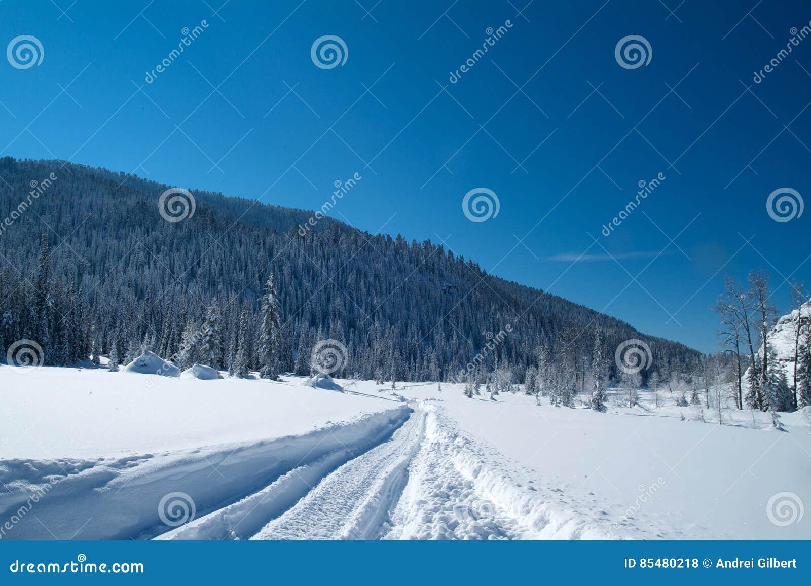 Σημάδι διαδρομής οχήματος για το χιόνι στο χιόνι ενάντια στα βουνά και έναν μπλε ουρανό