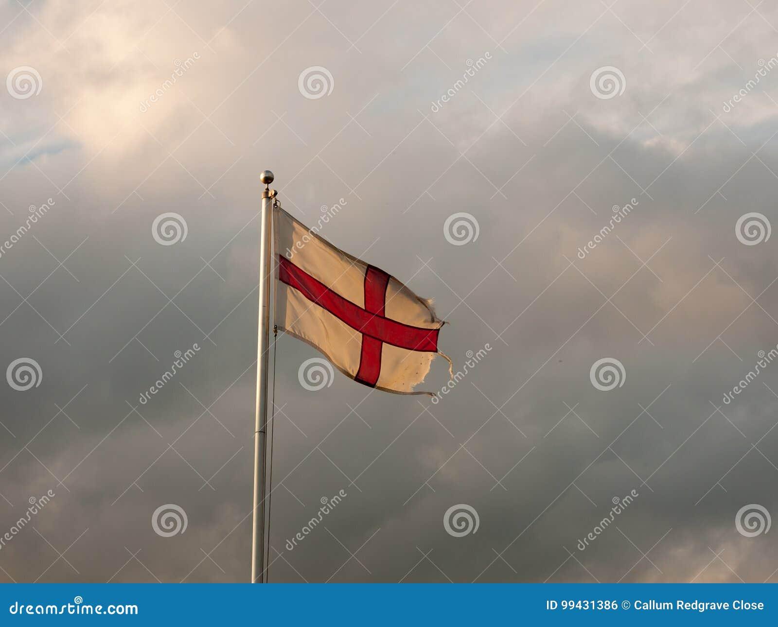 Σημαία της Αγγλίας που πετά με τους νεφελώδεις δραματικούς ουρανούς κατά τη διάρκεια του ηλιοβασιλέματος
