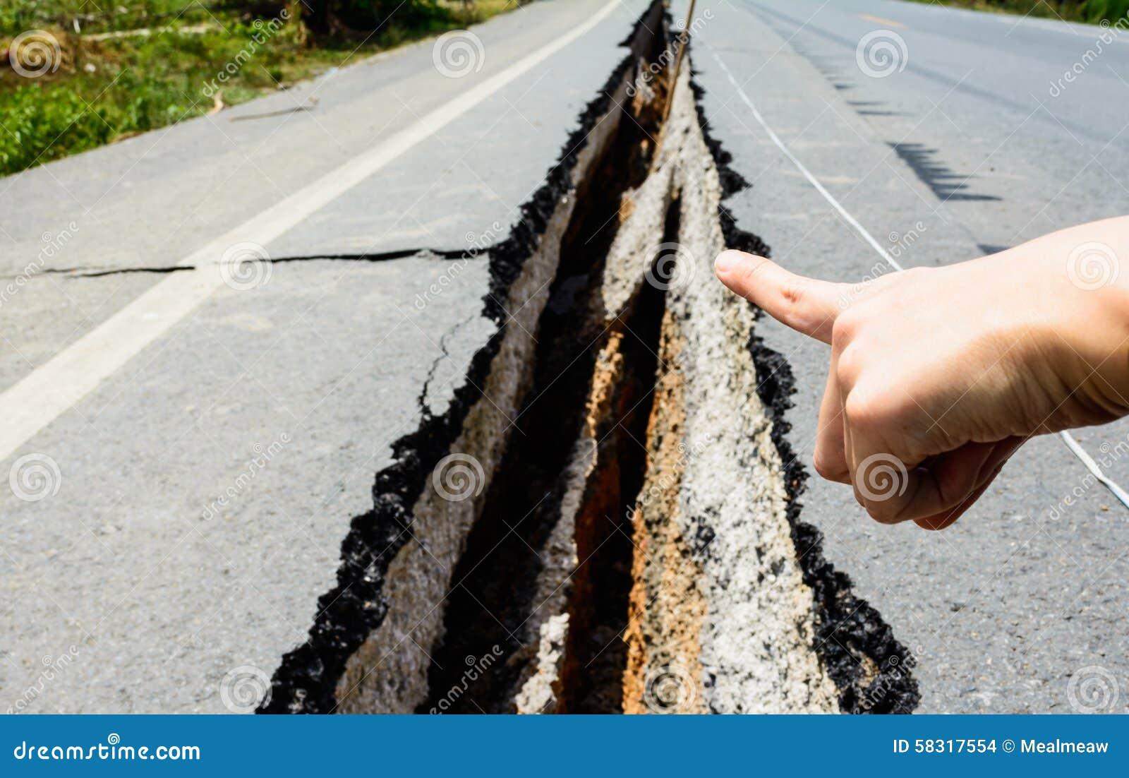 Σημείο χεριών στο ραγισμένο δρόμο, ραγισμένος οδικός aftetr σεισμός