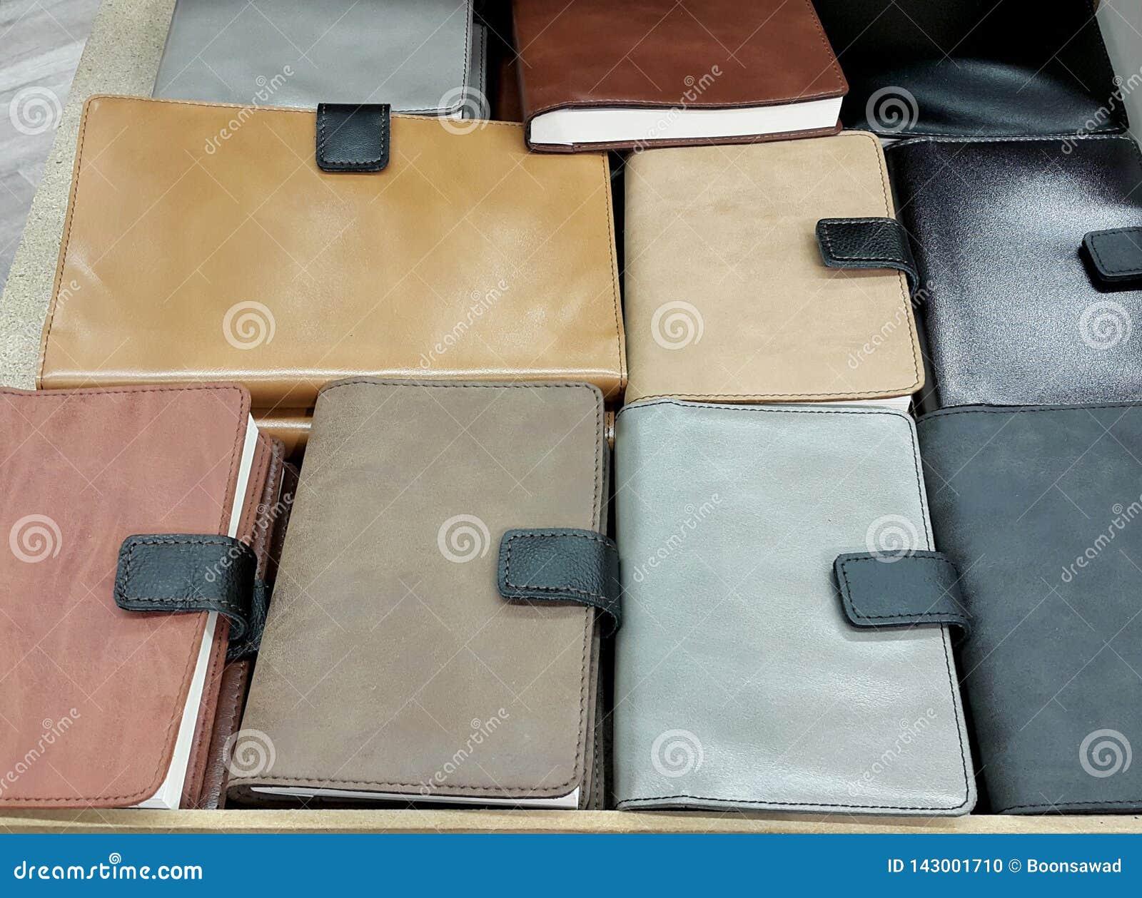 Σημειωματάρια κάλυψης δέρματος στο υπόβαθρο ραφιών