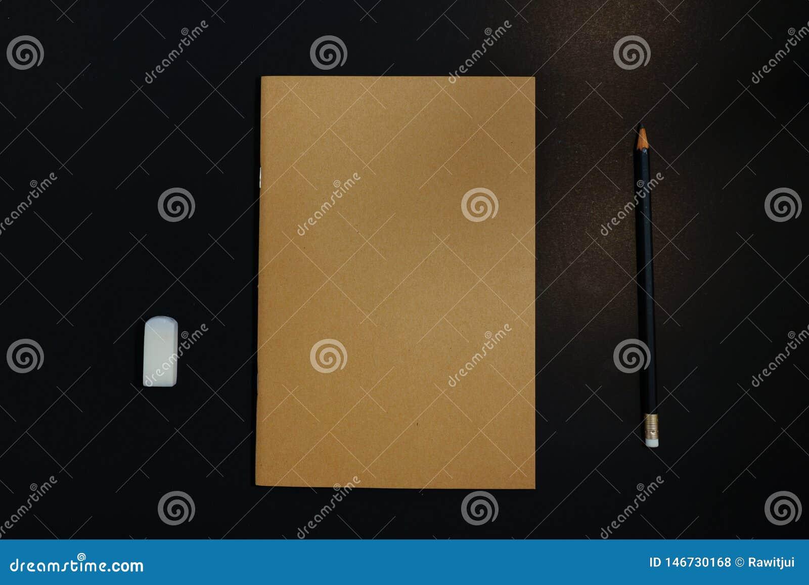 Σημειωματάριο, μολύβι και γόμα στο μαύρο υπόβαθρο