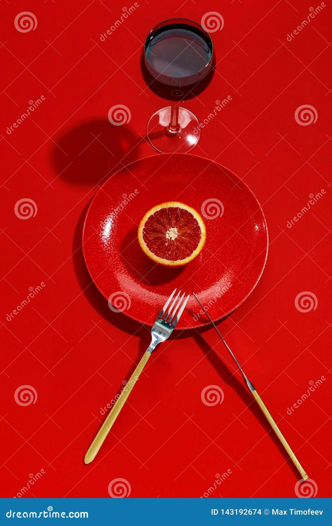 Σισιλιάνο πορτοκάλι που κόβεται στο μισό σε ένα κόκκινο πιάτο r r E