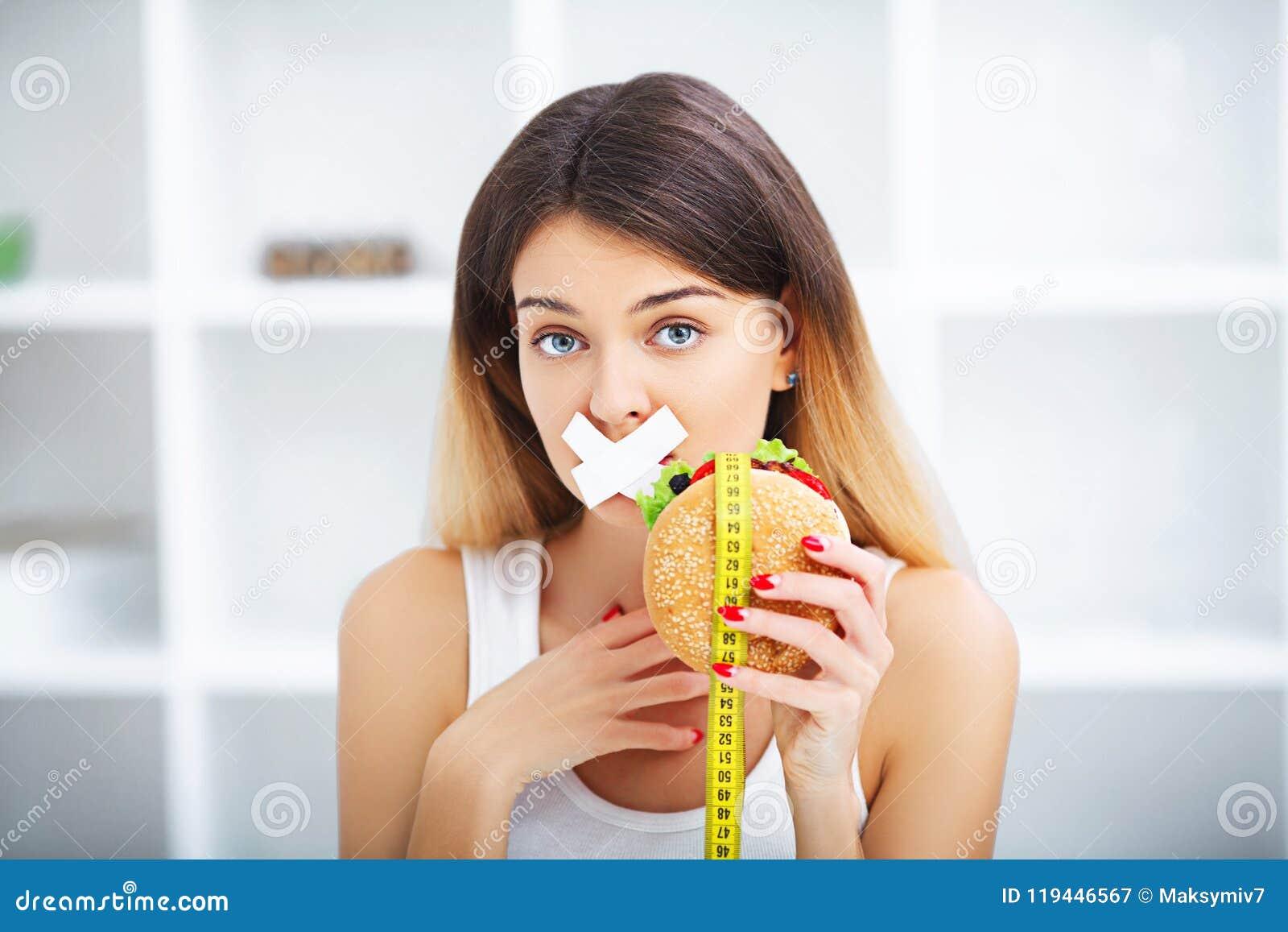 σιτηρέσιο Νέα όμορφη γυναίκα που τρώει burger, αυτό παλιοπράγματα ` s και unhealt