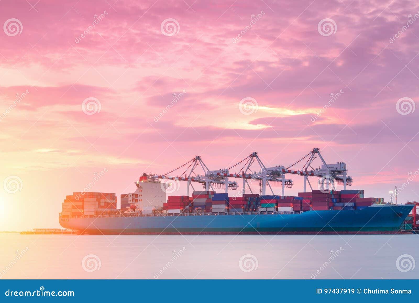 Σκάφος φορτίου φορτίου εμπορευματοκιβωτίων με τη λειτουργώντας γέφυρα γερανών στο ναυπηγείο στο σούρουπο για τη λογιστική εισαγωγ