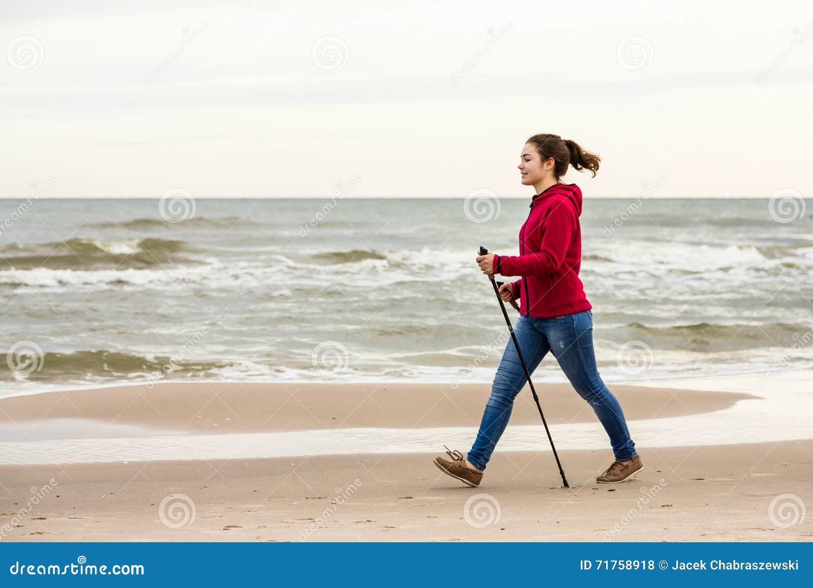 Σκανδιναβικό περπάτημα - νέο κορίτσι που επιλύει στην παραλία