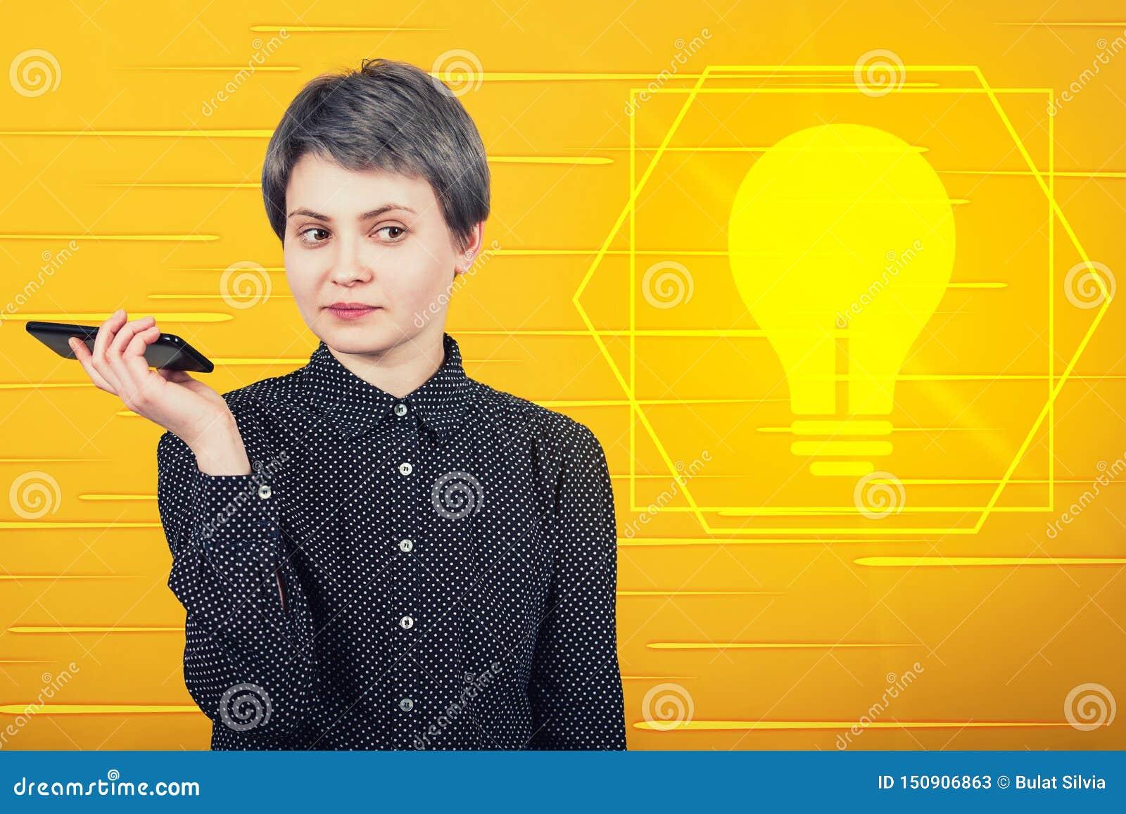 Σκεπτική επιχειρηματίας που κρατά το κινητό τηλέφωνο σκέψη μια καινοτόμο ιδέα ως σύμβολο λαμπών φωτός που λάμπει σε κίτρινο
