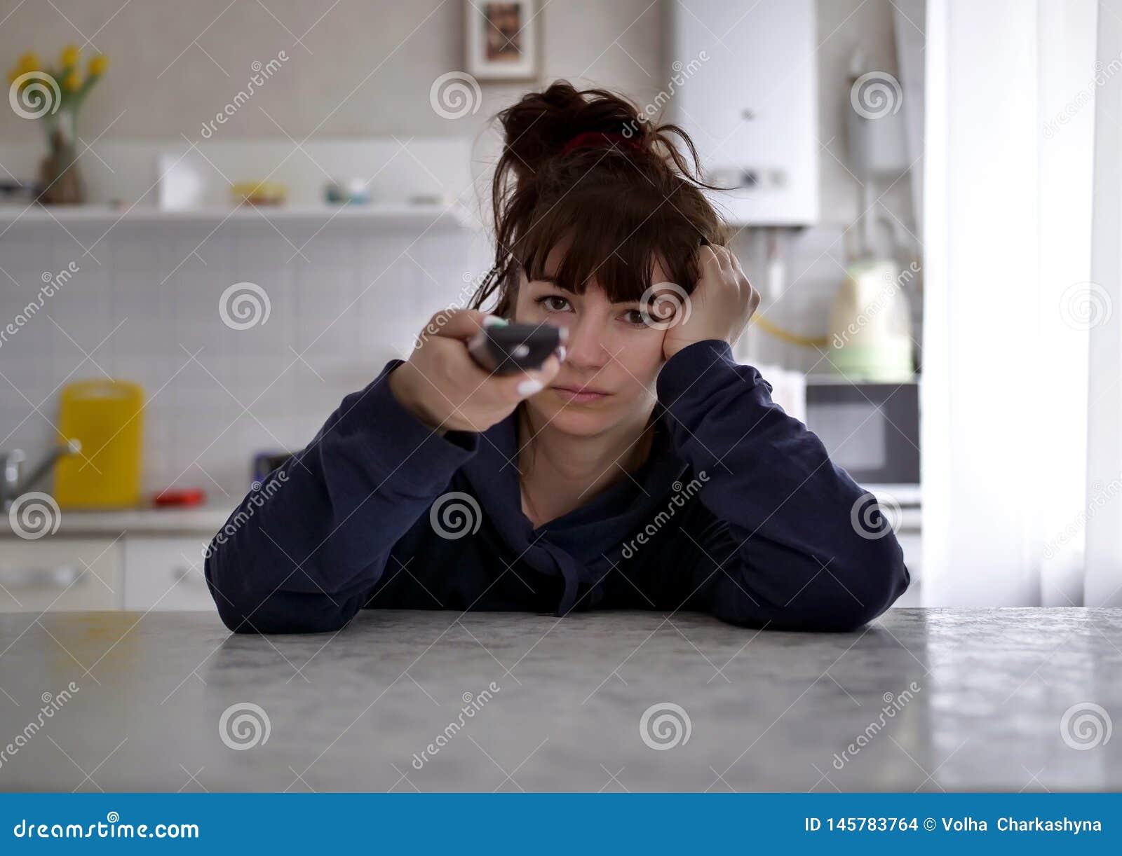 Σκεπτική νέα συνεδρίαση γυναικών με τον τηλεχειρισμό σχετικά με ένα θολωμένο υπόβαθρο της κουζίνας